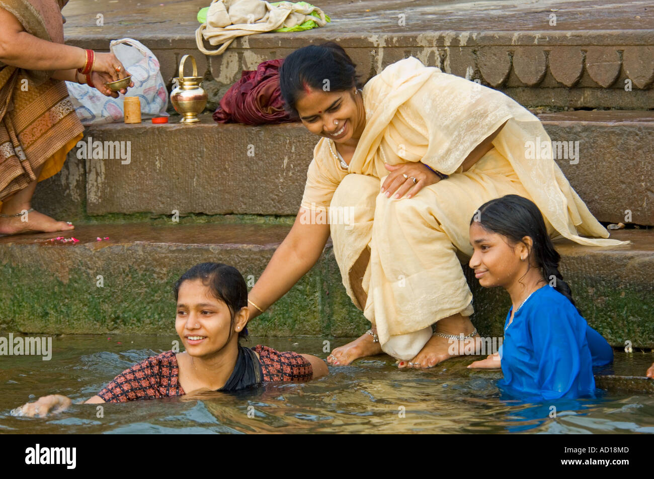 Close up two young Indian girls with their mother bathing ...
