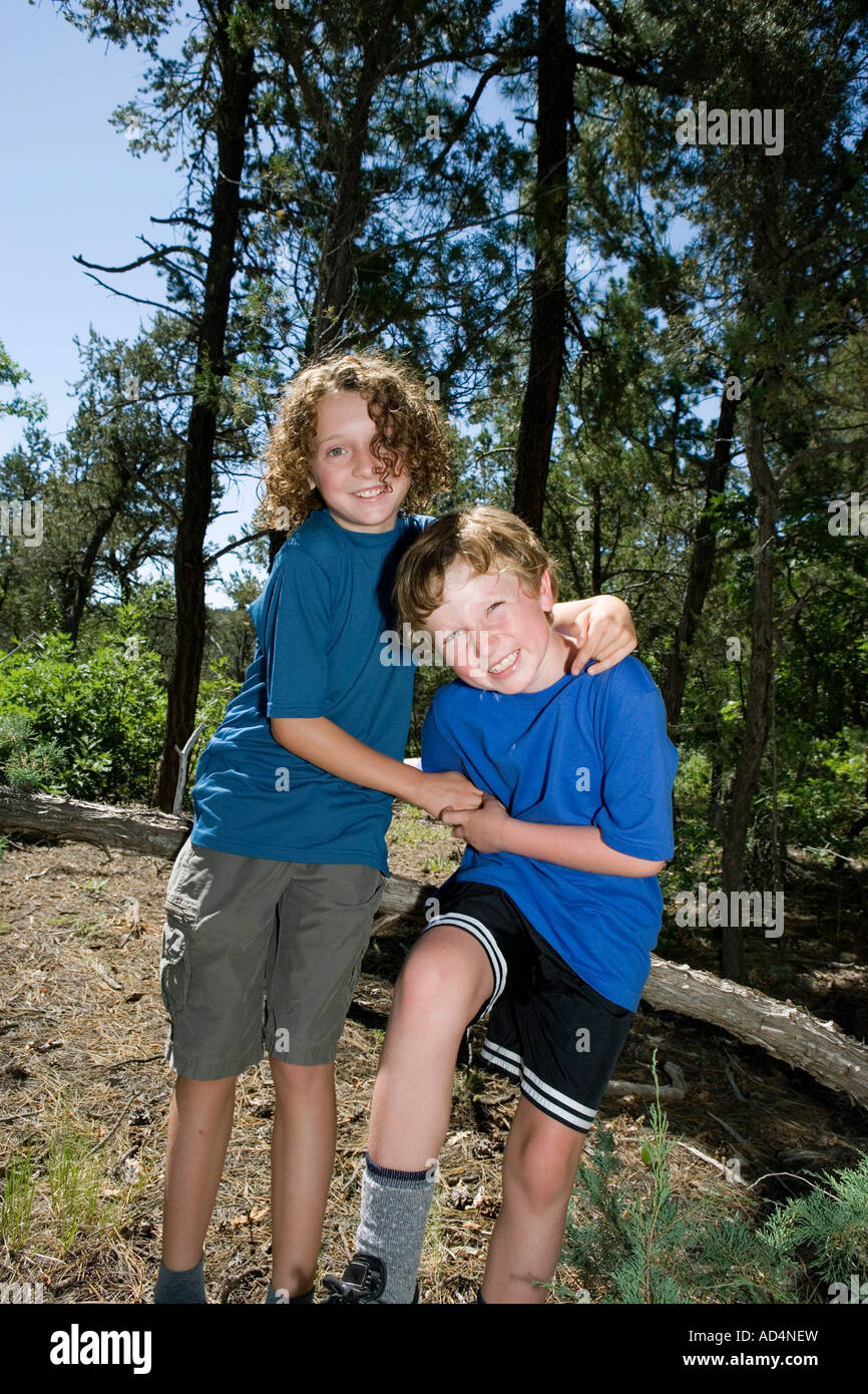 Two Young Boys Play Fighting In A Forest