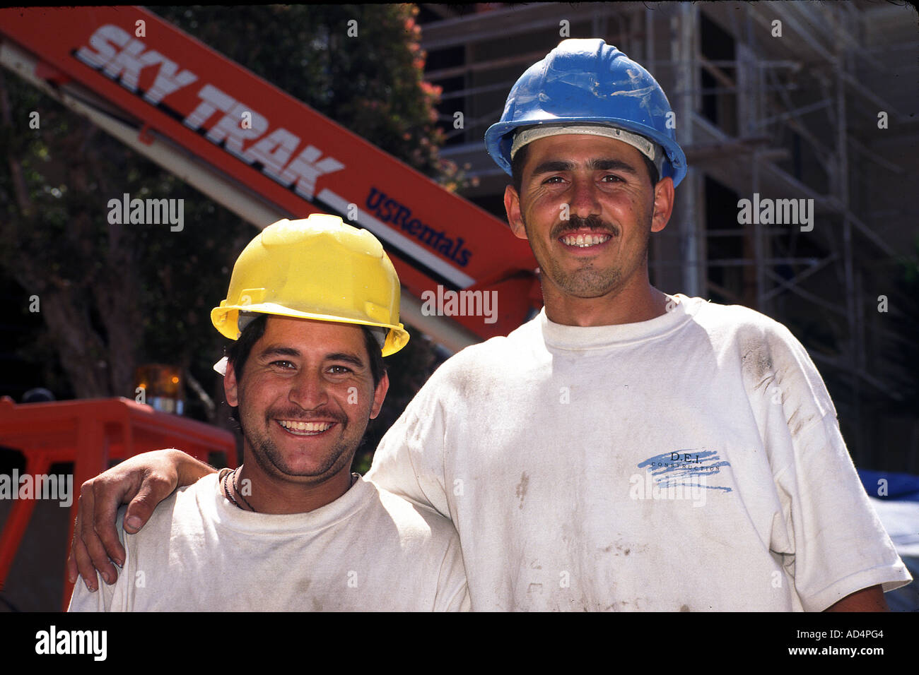 Two Happy Mexican Construction Workers Pose In Front Of Site