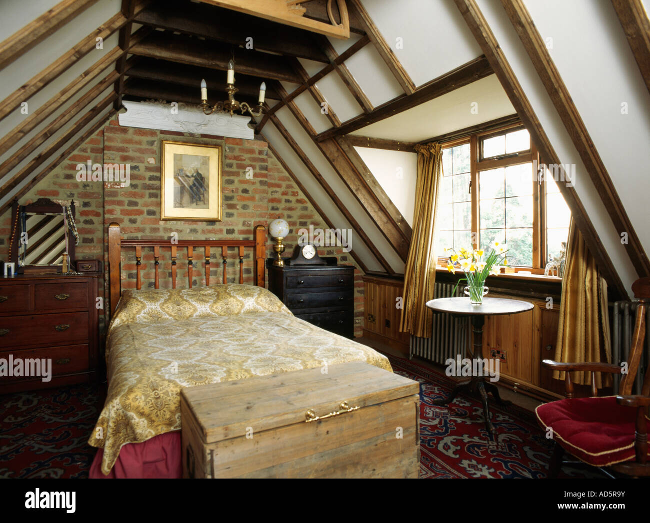 Attic Bed wooden chest below bed in attic bedroom with brick wall and beamed