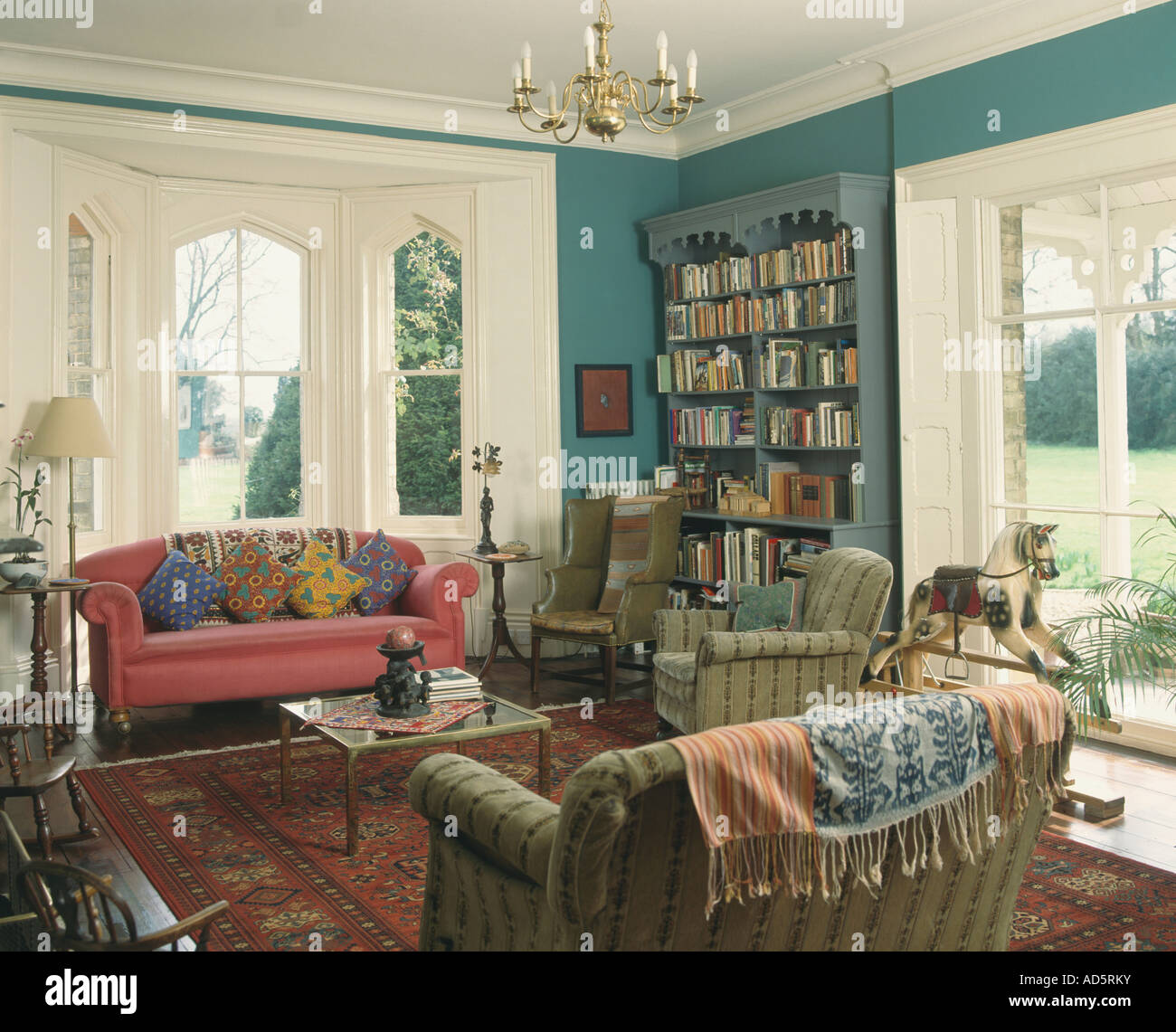 Colourful cushions and throws on sofas in blue livingroom with ...