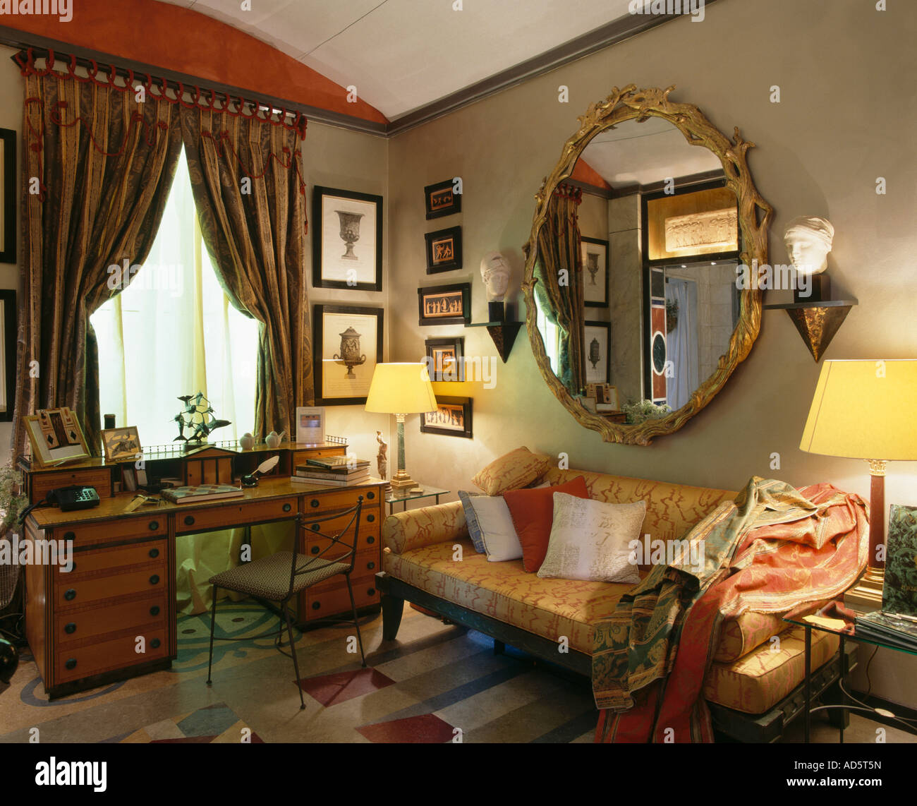 Ornate Gilt Circular Mirror Above Sofa In Livingroom With Lighted Lamps And Antique Desk