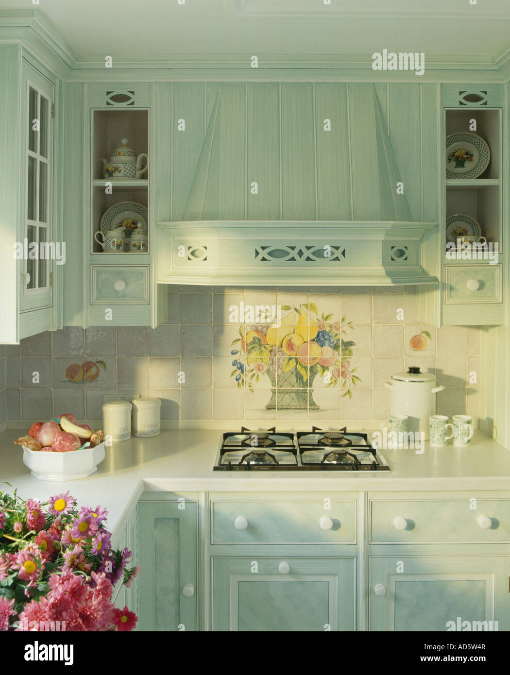 Corner Of Pastel Turquoise Kitchen With Floral Tiles Above Built In Hob And Distressed Paint Effect On Cupboards