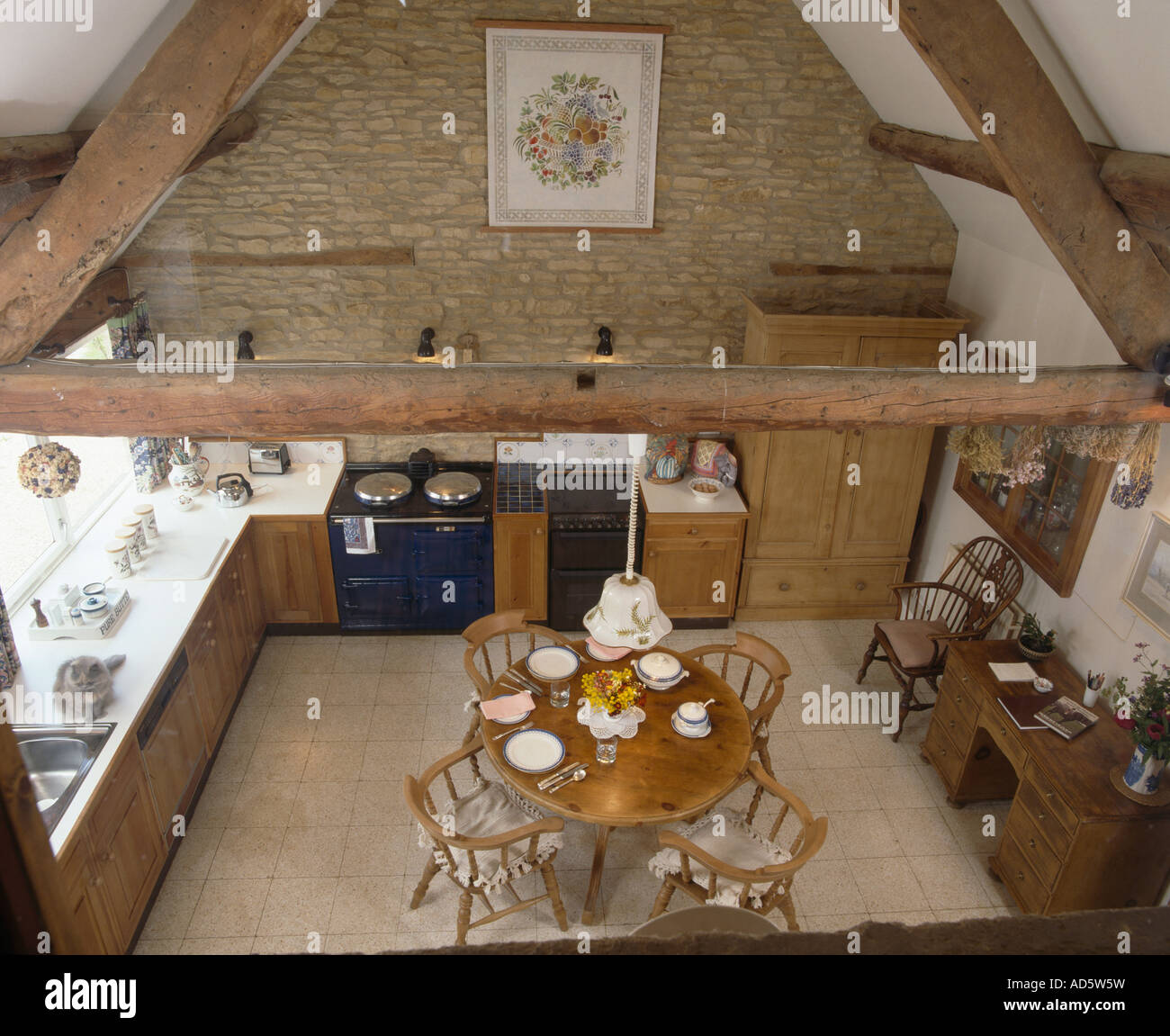 Barn Conversion Kitchens aerial view of circular wooden dining table and chairs in barn