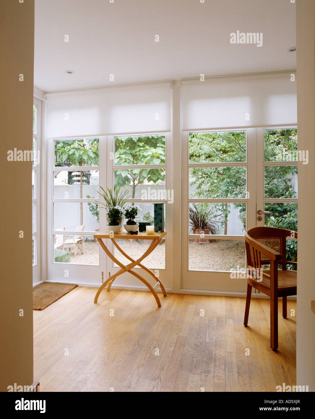 Wooden Flooring In Modern White Dining Room Extension With View Of Courtyard Garden Through Glass Doors Blinds
