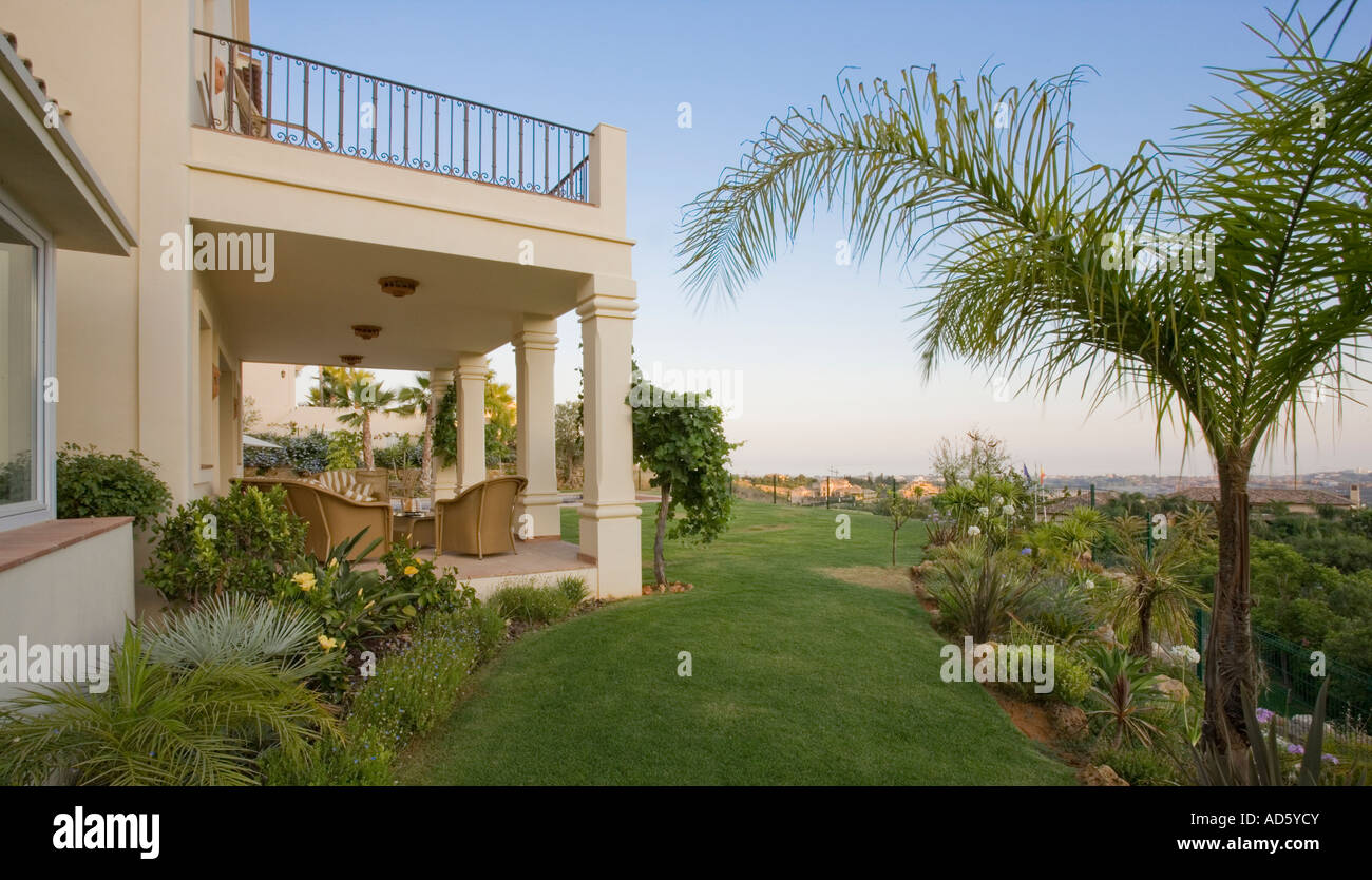 palm tree and lawn in garden of modern spanish villa with wicker