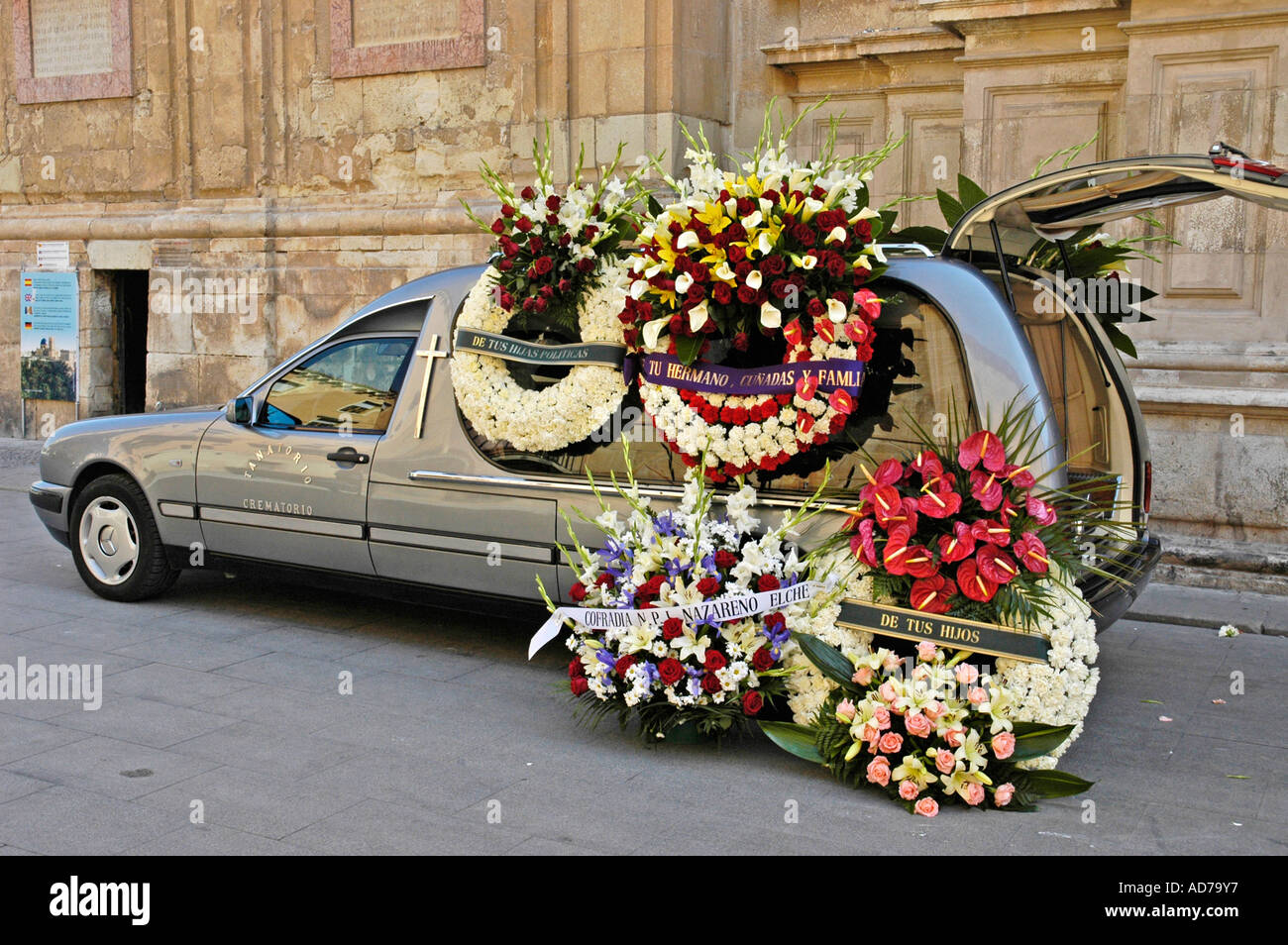 Hearse with mourning wreaths in front of the church at a funeral basilica santa maria