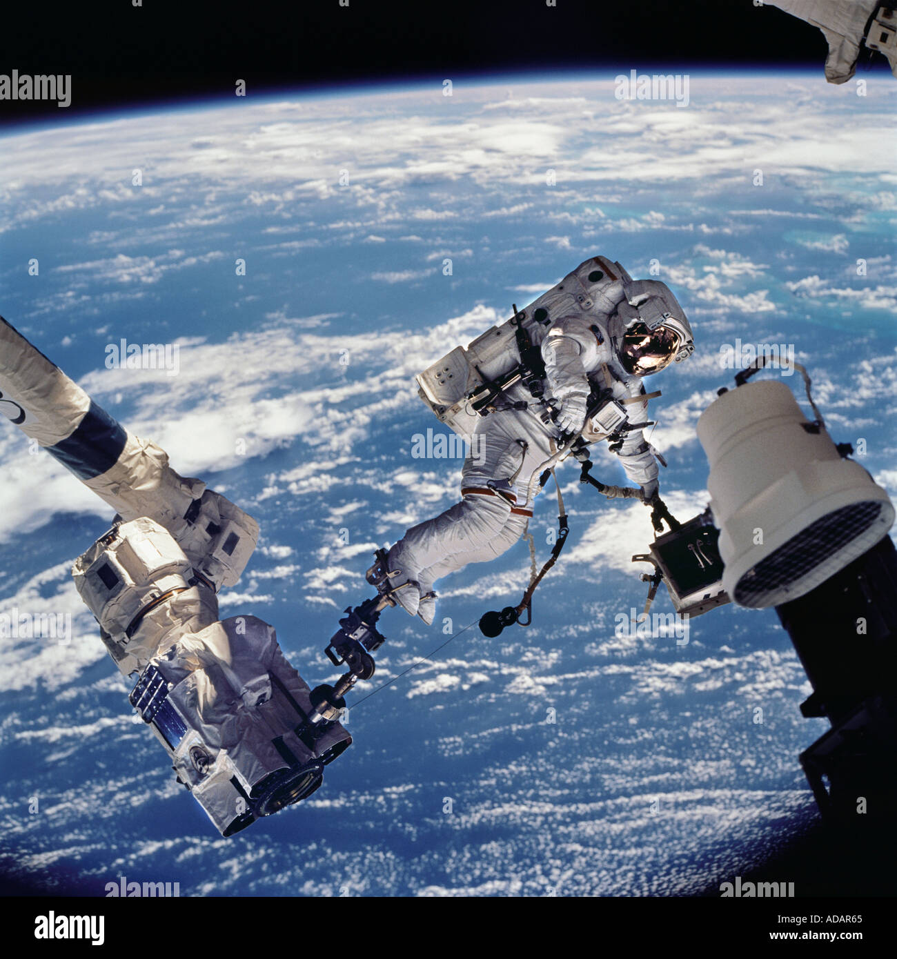 Astronaut on extended robotic arm, Space Shuttle Stock ...