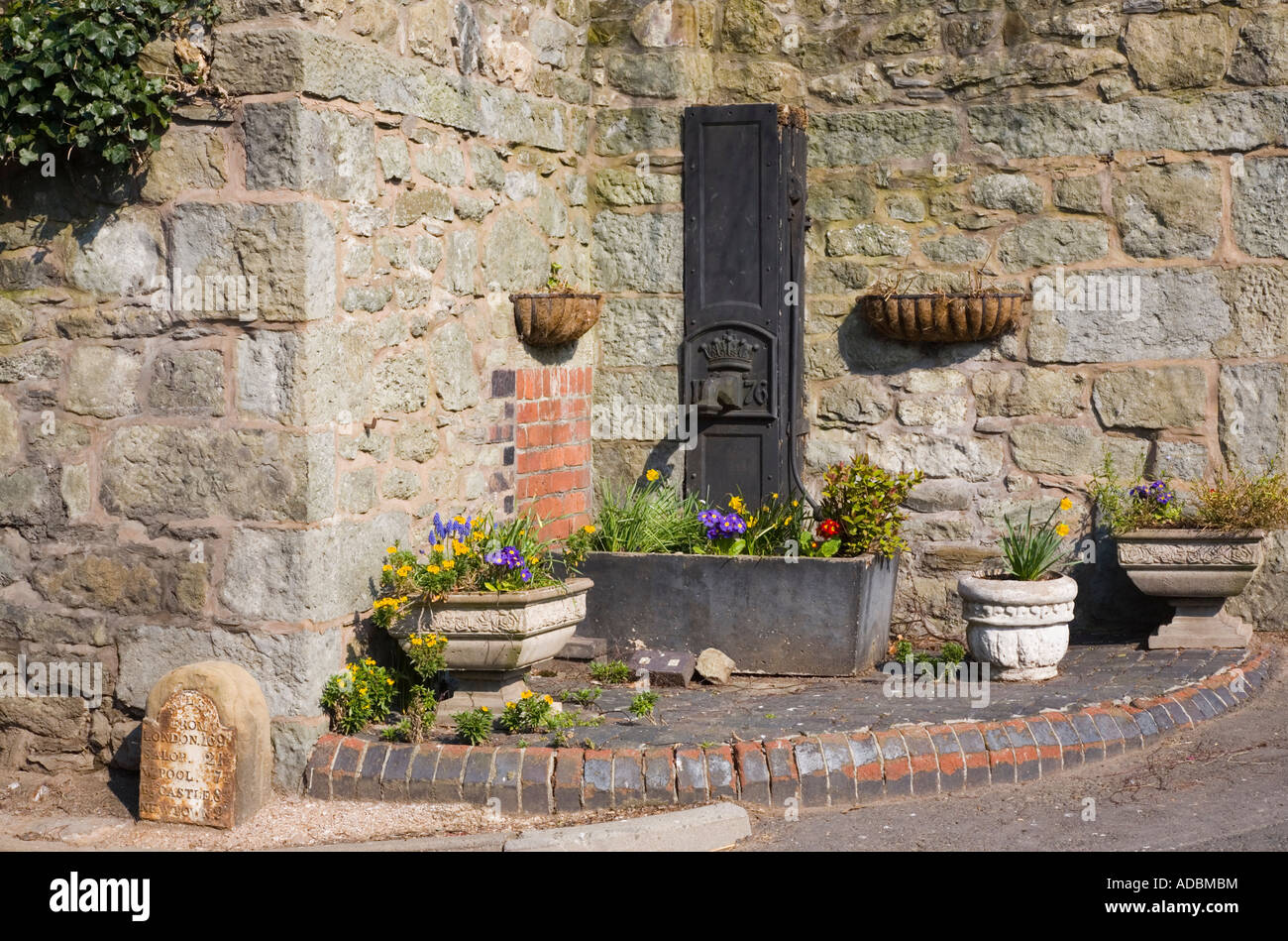 montgomery powys mid wales uk looking down to the square of old imperial milestone 19th century town water pump 1876 and flower trough by wall montgomery powys