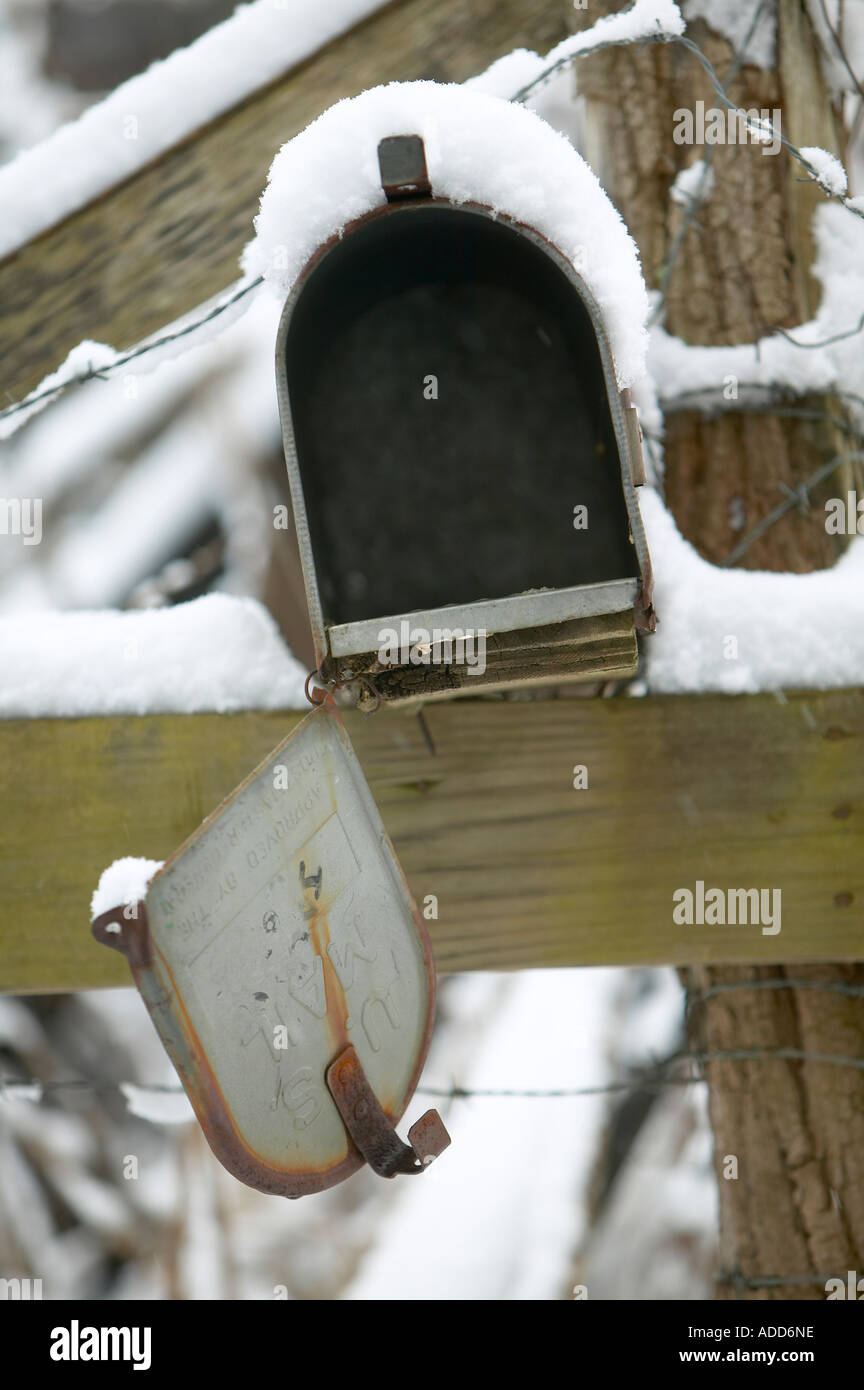 Mailbox With Broken Door Hanging By One Hinge Covered With Snow   Stock  Image