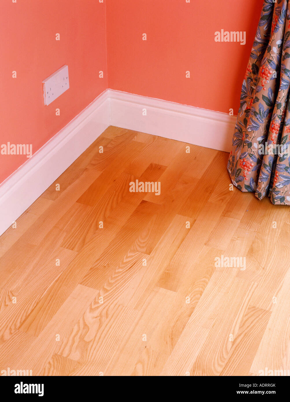Corner Of Room With Laminate Wood Floor And White Skirting Board Below Red Wall