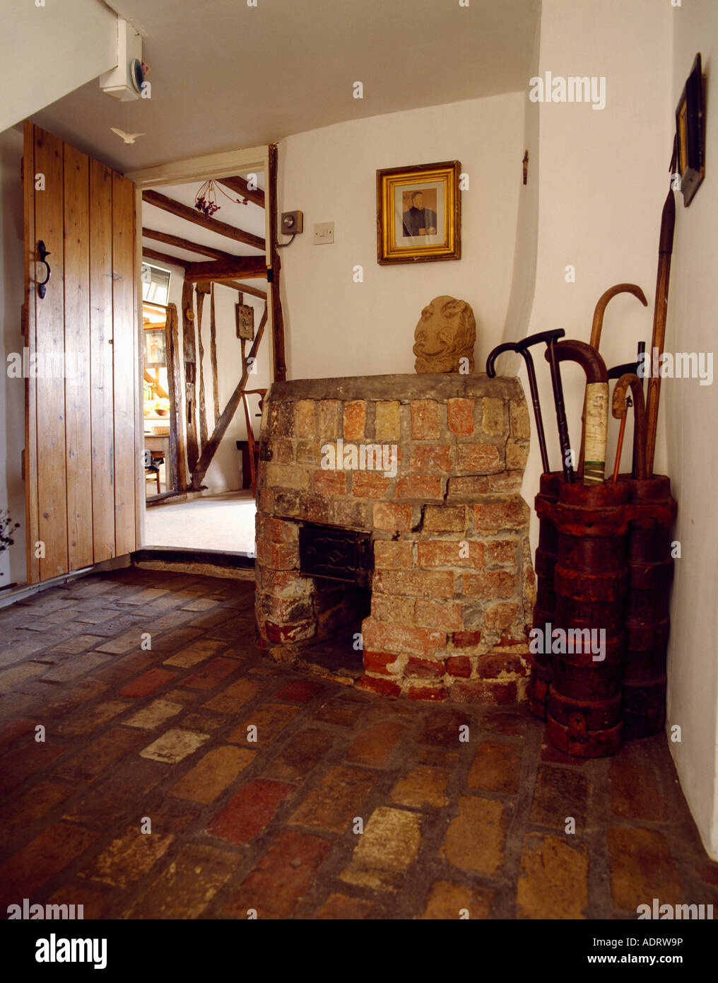 old brick fireplace in the corner of cottage hall with brick floor