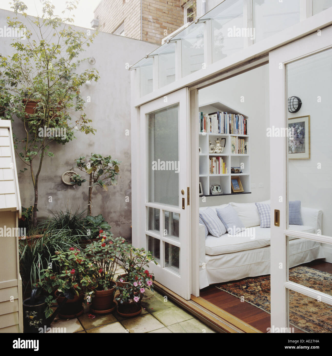 View from courtyard garden of white sofa in modern white living