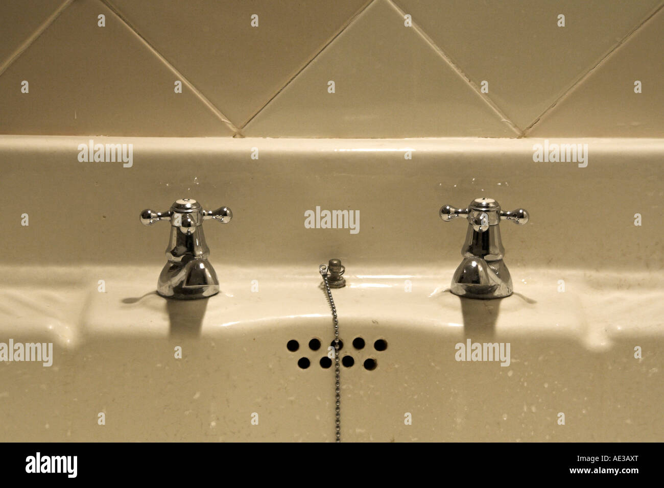 old bathroom washbasin with old taps, in a tiled wall Stock Photo ...