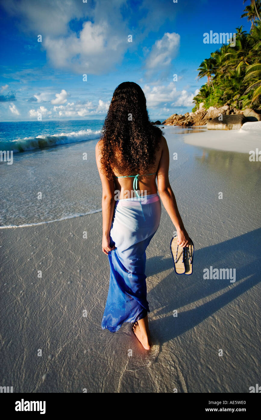 Woman walking on a beach royalty - Woman Walking On Beach Anse Victorin Beach And Palm Trees Fregate Island Seychelles