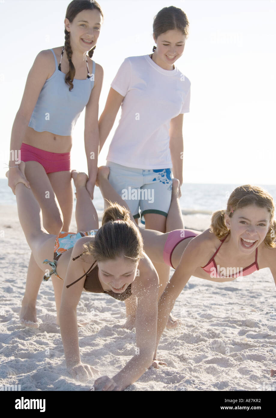 girls like feet Preteen girls holding friends' feet like wheelbarrows on beach