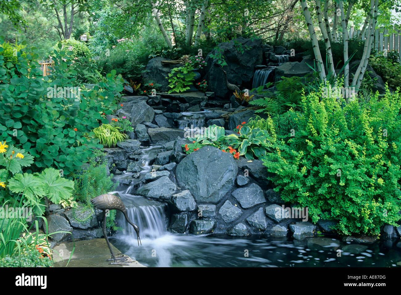 sloping minnesota backyard garden includes waterfall pond stock