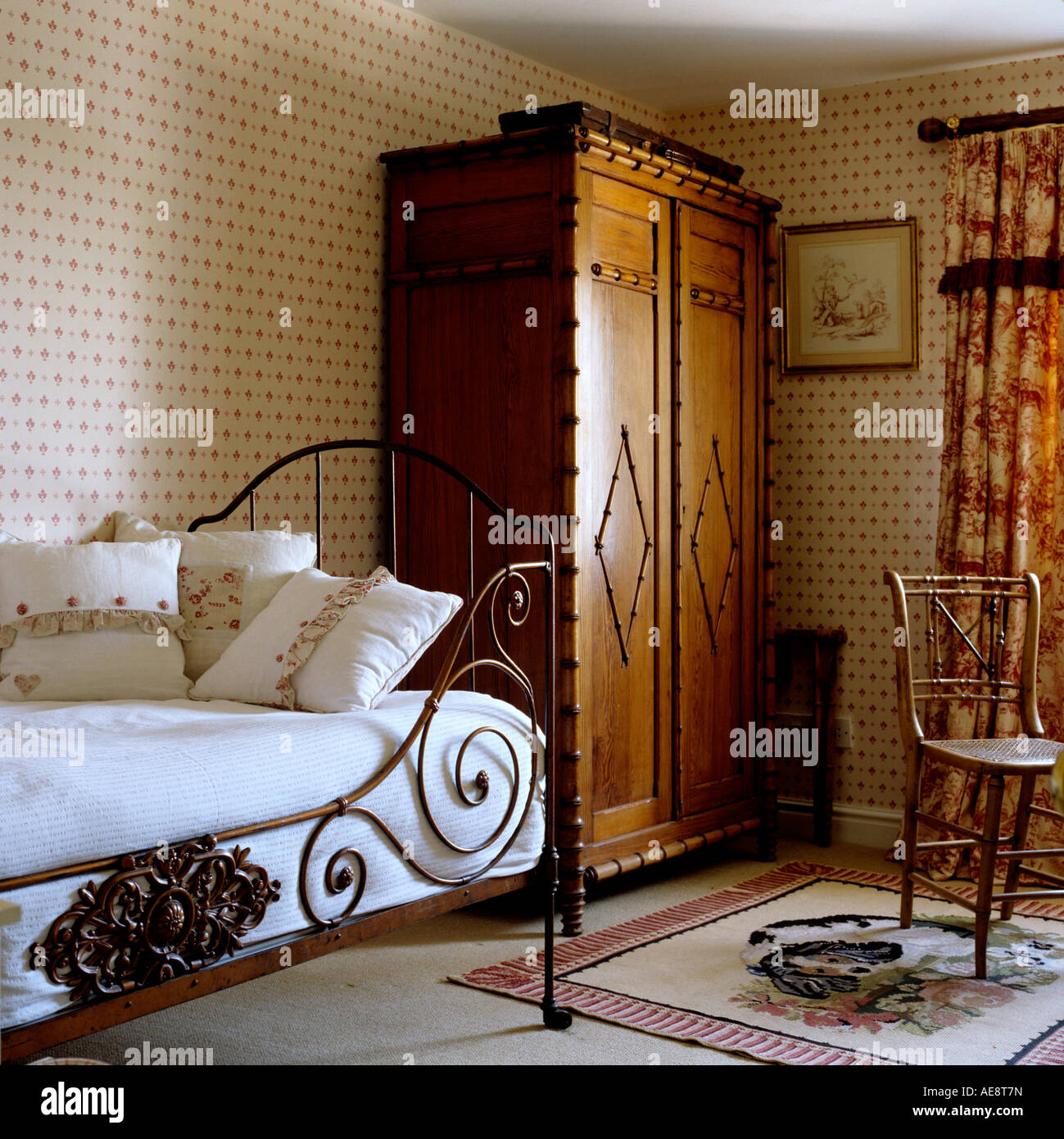 victorian wrought iron bed and large wardrobe in bedroom of english country house stock photo