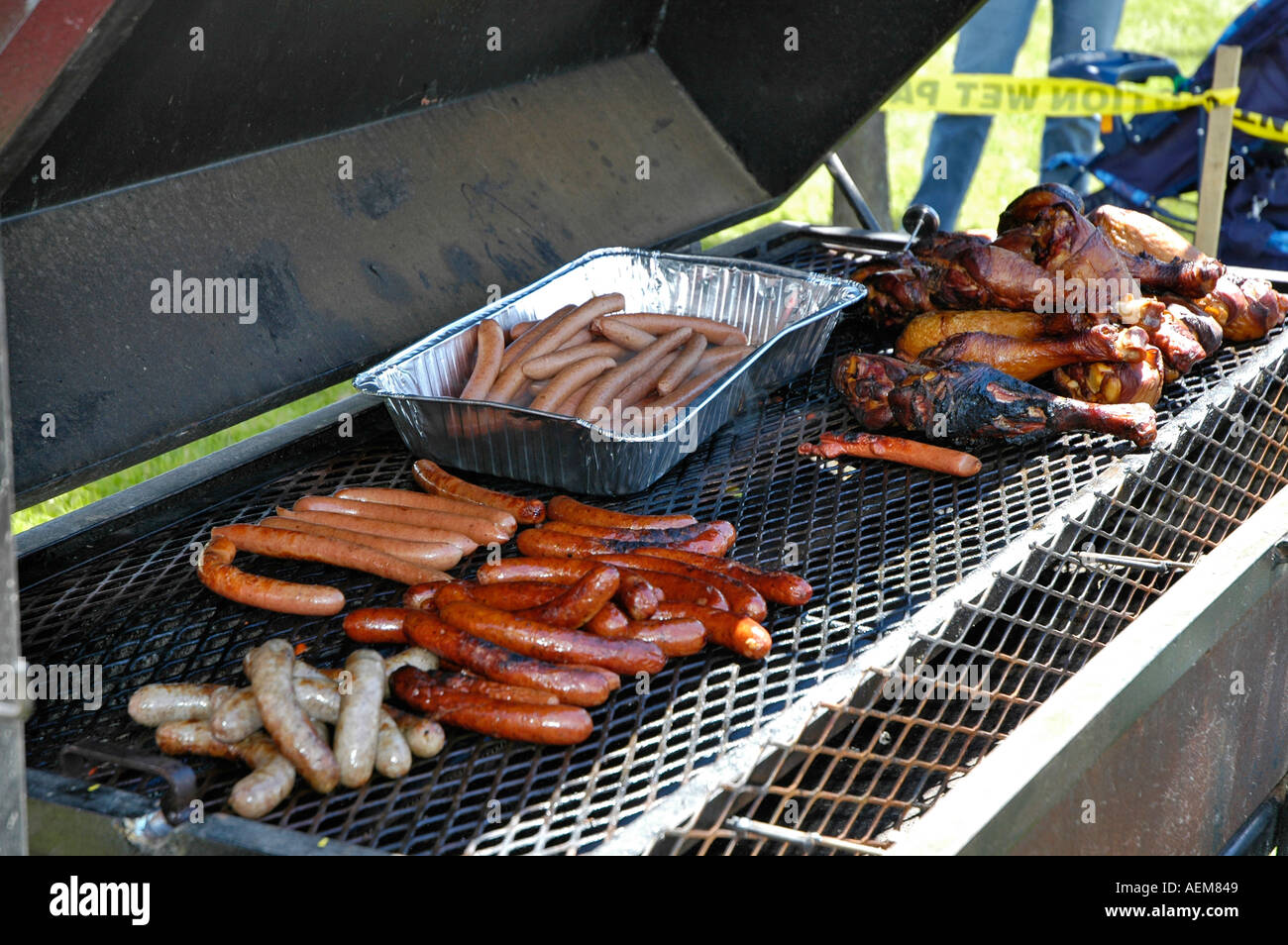 Male prepares turkey legs hamburgers and hot dogs on a large grill ...