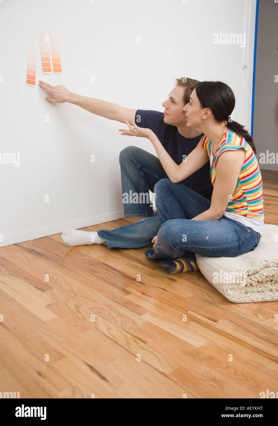 Couple Looking At Paint Swatches On Wall