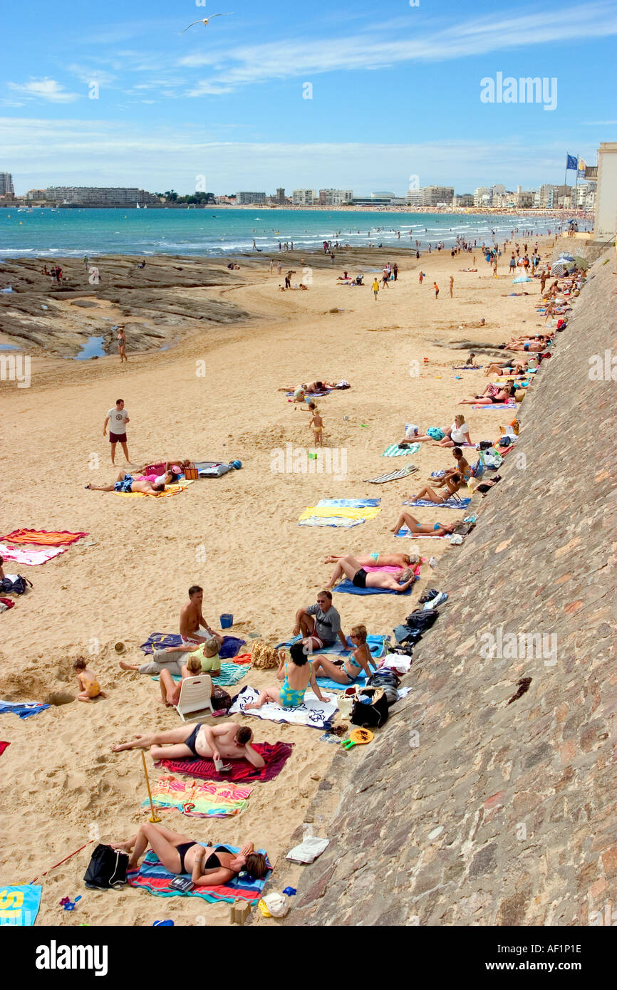 people on a white sandy beach sun tanning and enjoying ...