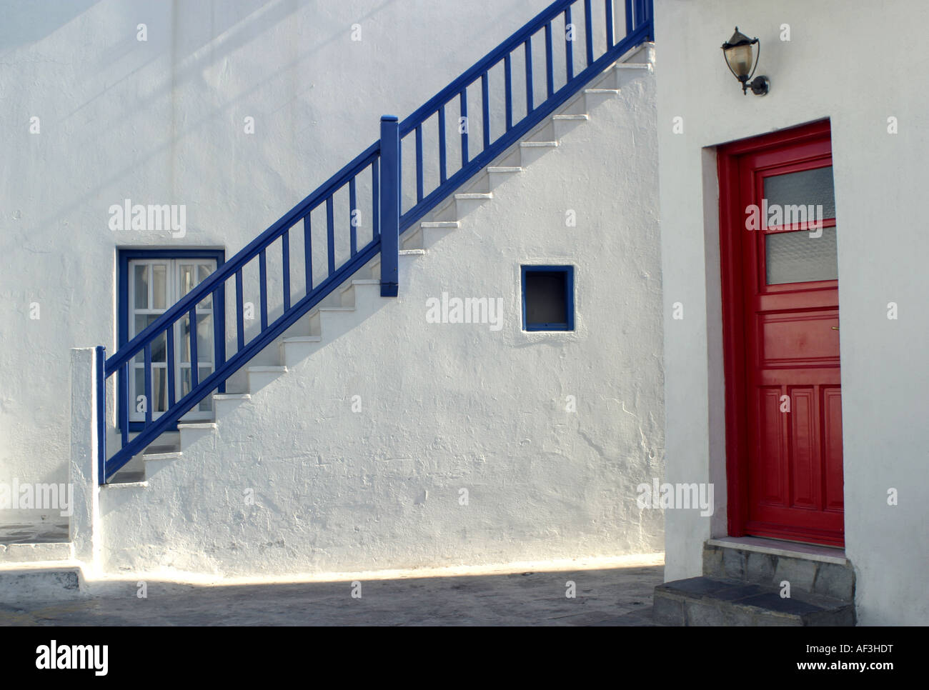 A Whitewashed Building And Stairs Showing Blue Shutters And A Red Door