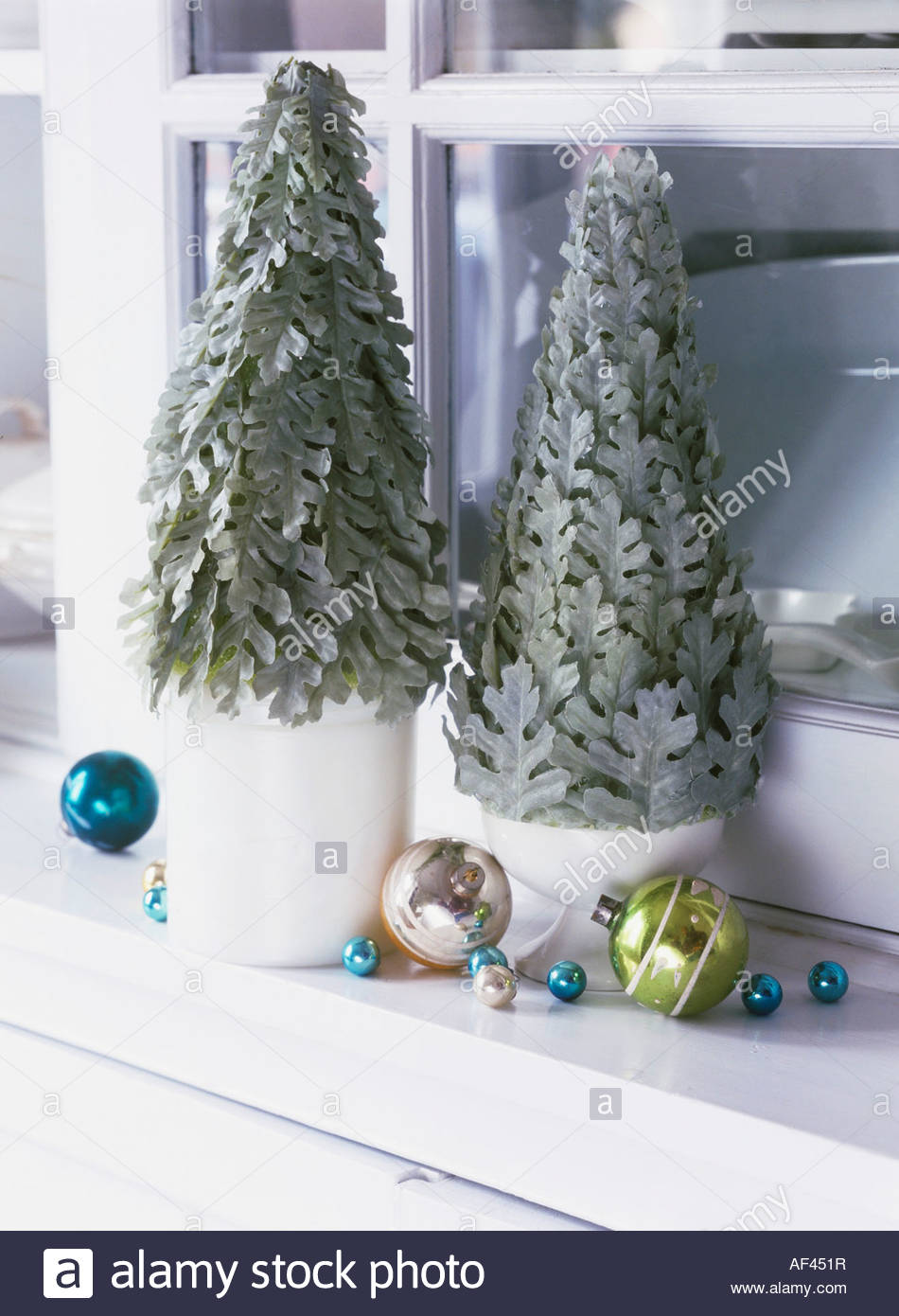 Small christmas trees with baubles on a window sill stock