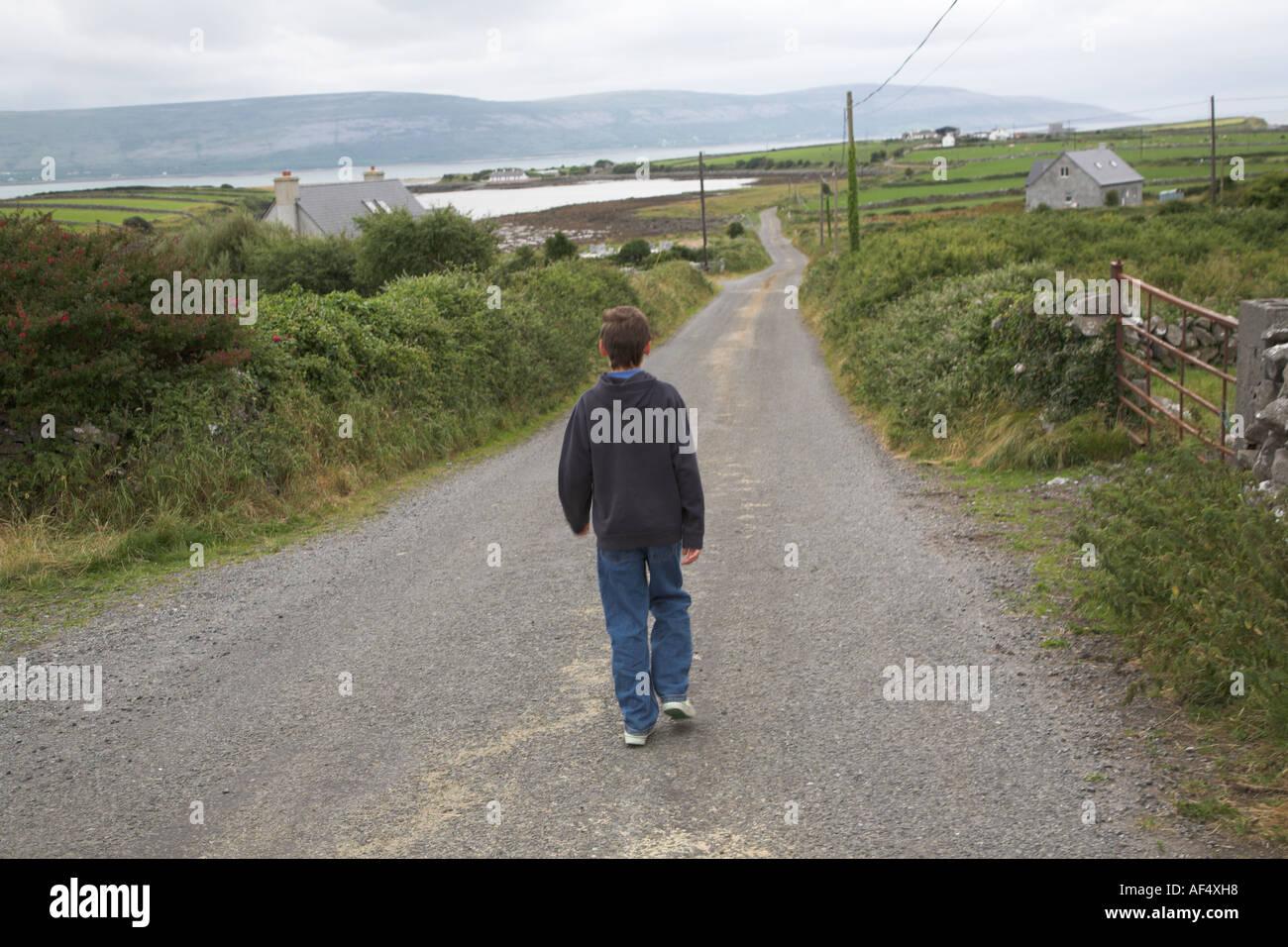boy walking alone on road - photo #5
