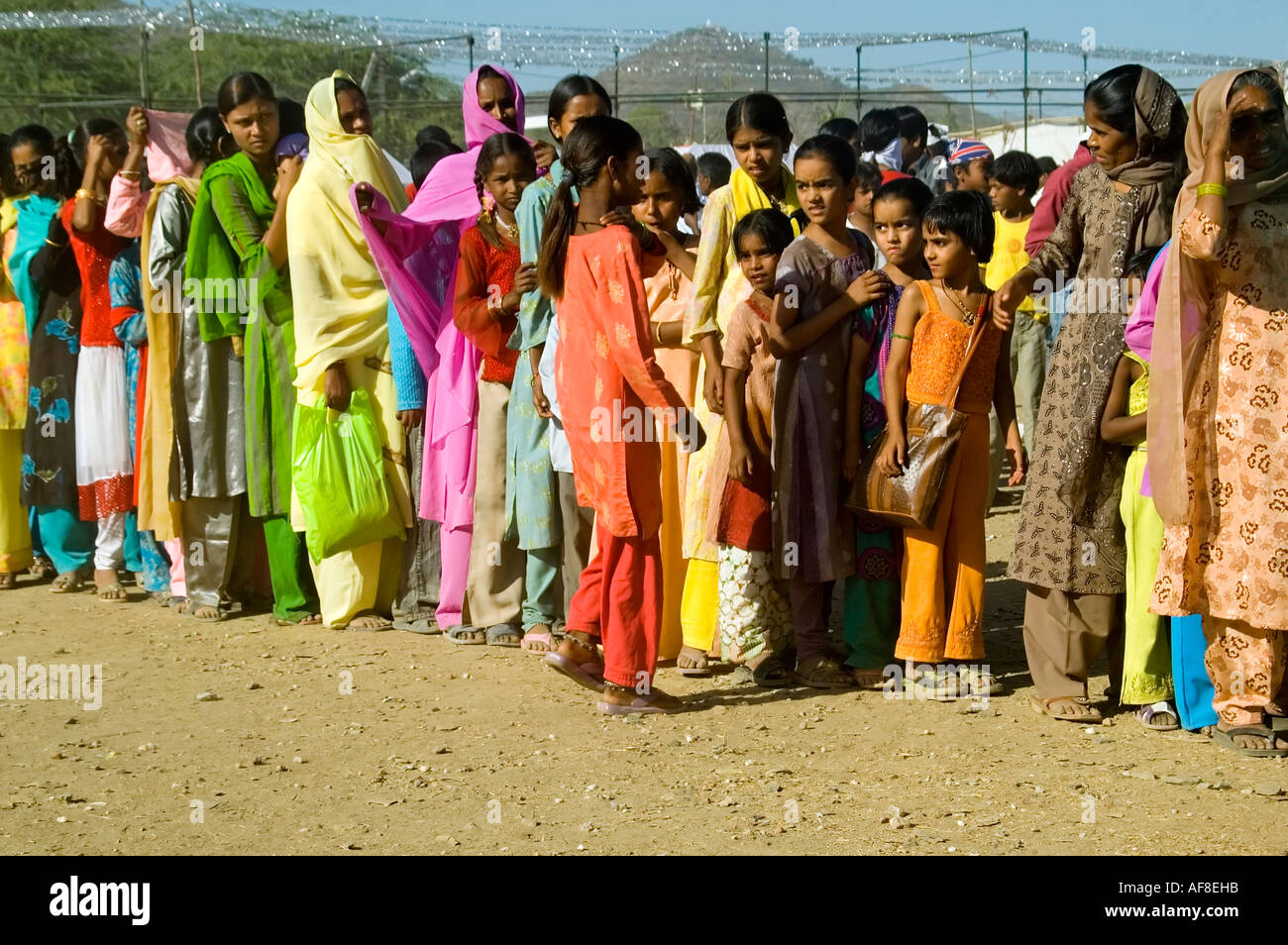 Desperate to use the bathroom - Humorous Horizontal Wide Angle Of A Long Queue Of Indian Ladies Waiting For The Toilet