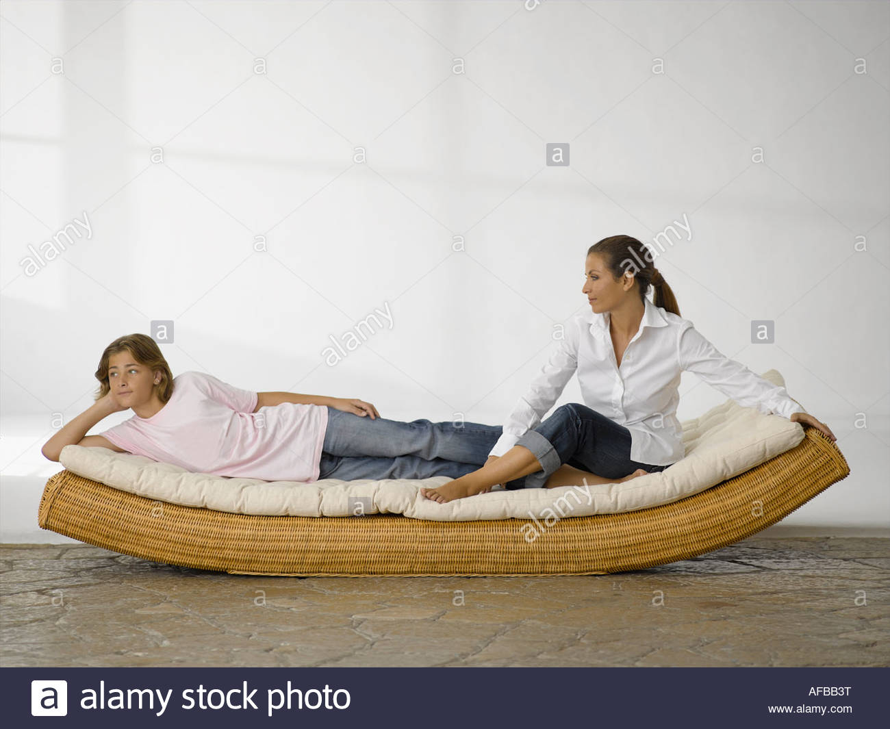Mid Adult Woman Sitting And Her Son Lying On A Rocking Bed Stock