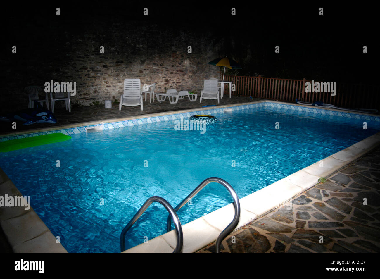 French Swimming Pool At Night With Plastic Chairs Stock