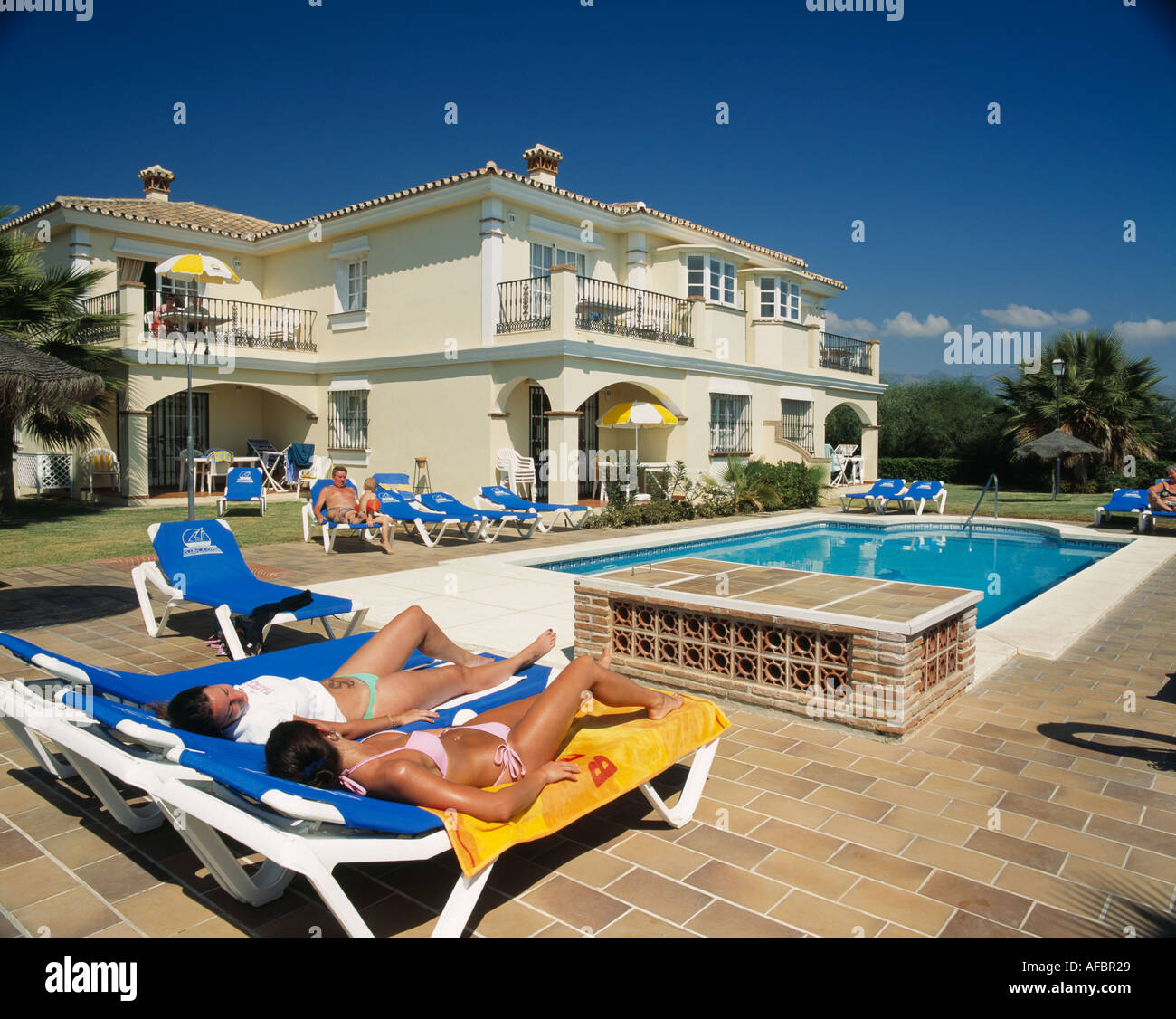 Hotel pool with people  People sunbathing on loungers on terrace beside swimming pool in ...