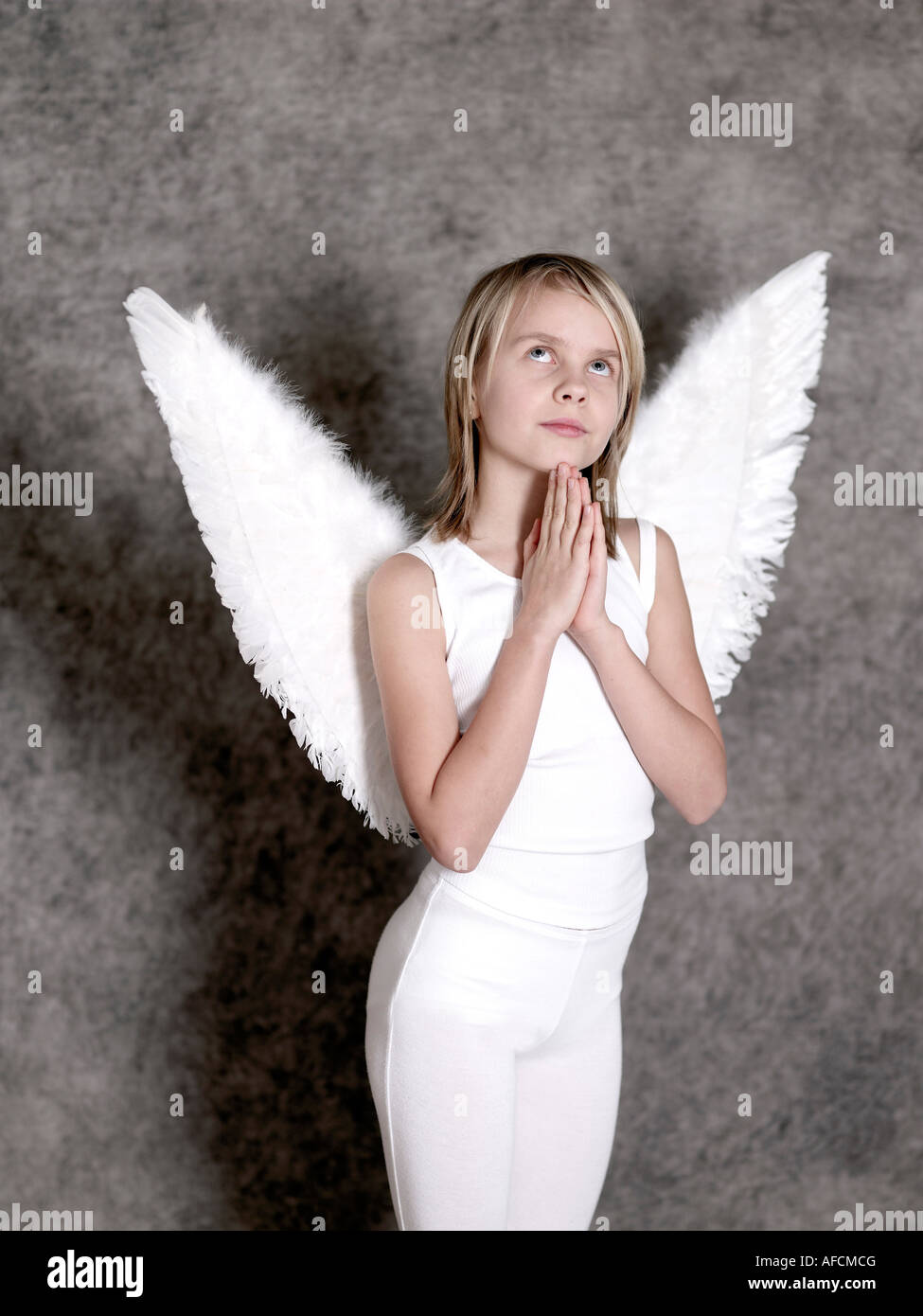 dressed up in angel wings praying and looking up stock photo