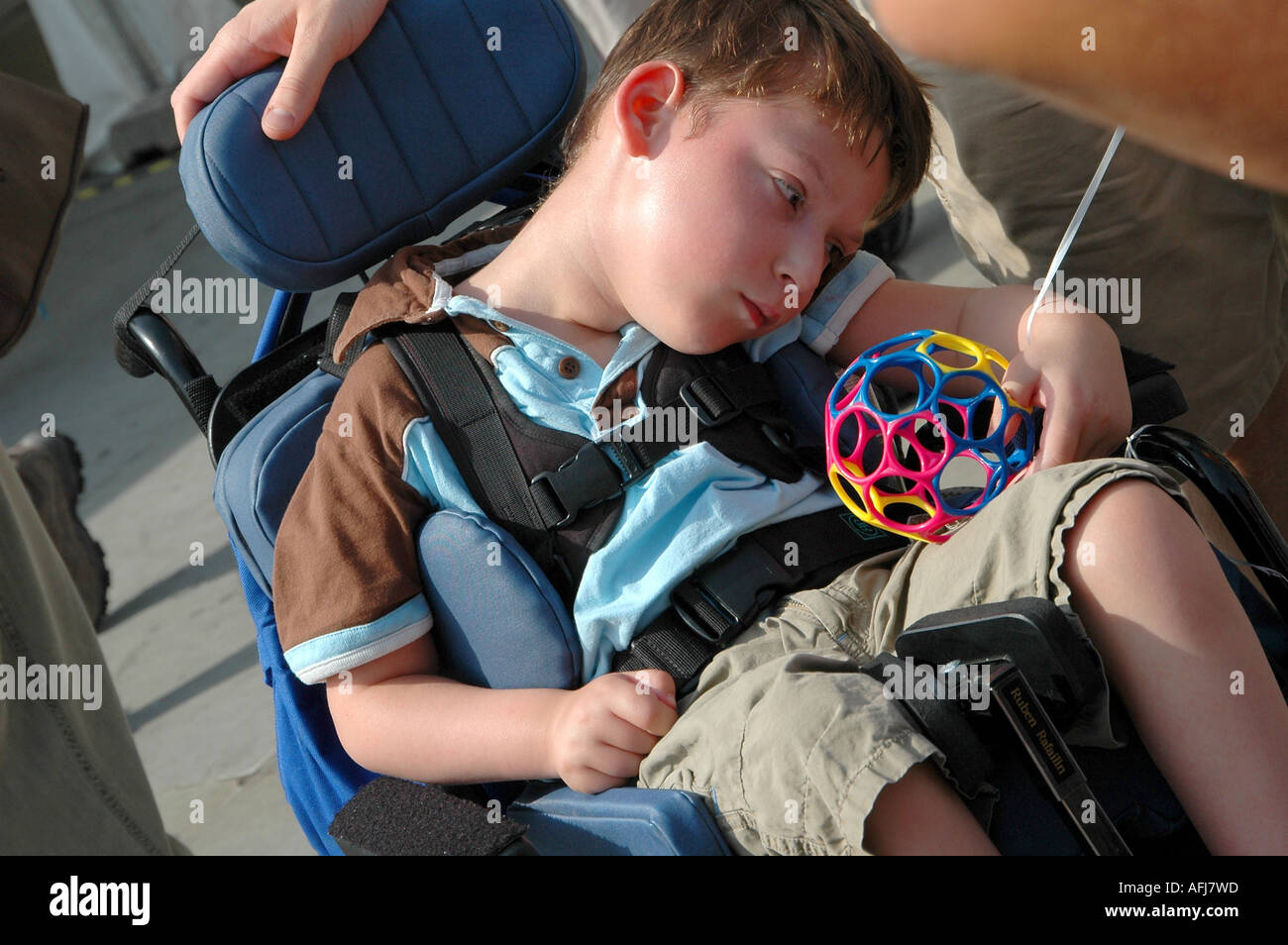 Disabled child in a wheelchair looking very sadly at his ...