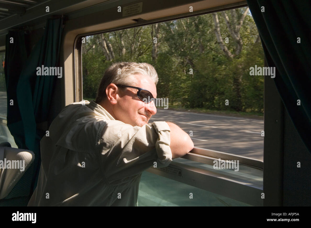 Ordinaire Middle Aged Man In A Travelling Shirt And Sunglasses Leaning On His Elbows  Out The Window Of Italian Train Car With Sun On Face