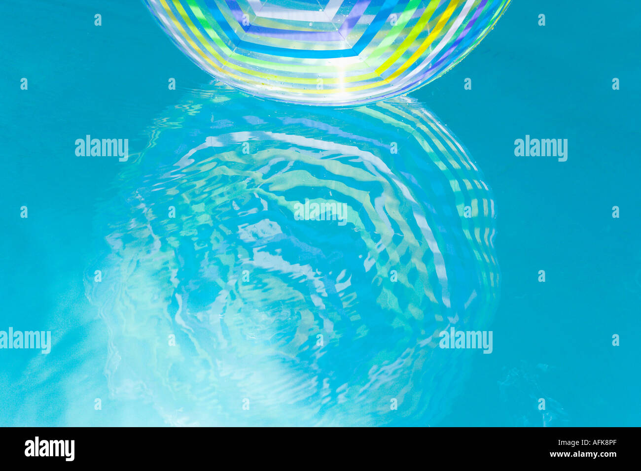 Pool Water With Beach Ball beach ball reflection in swimming pool water stock photo, royalty