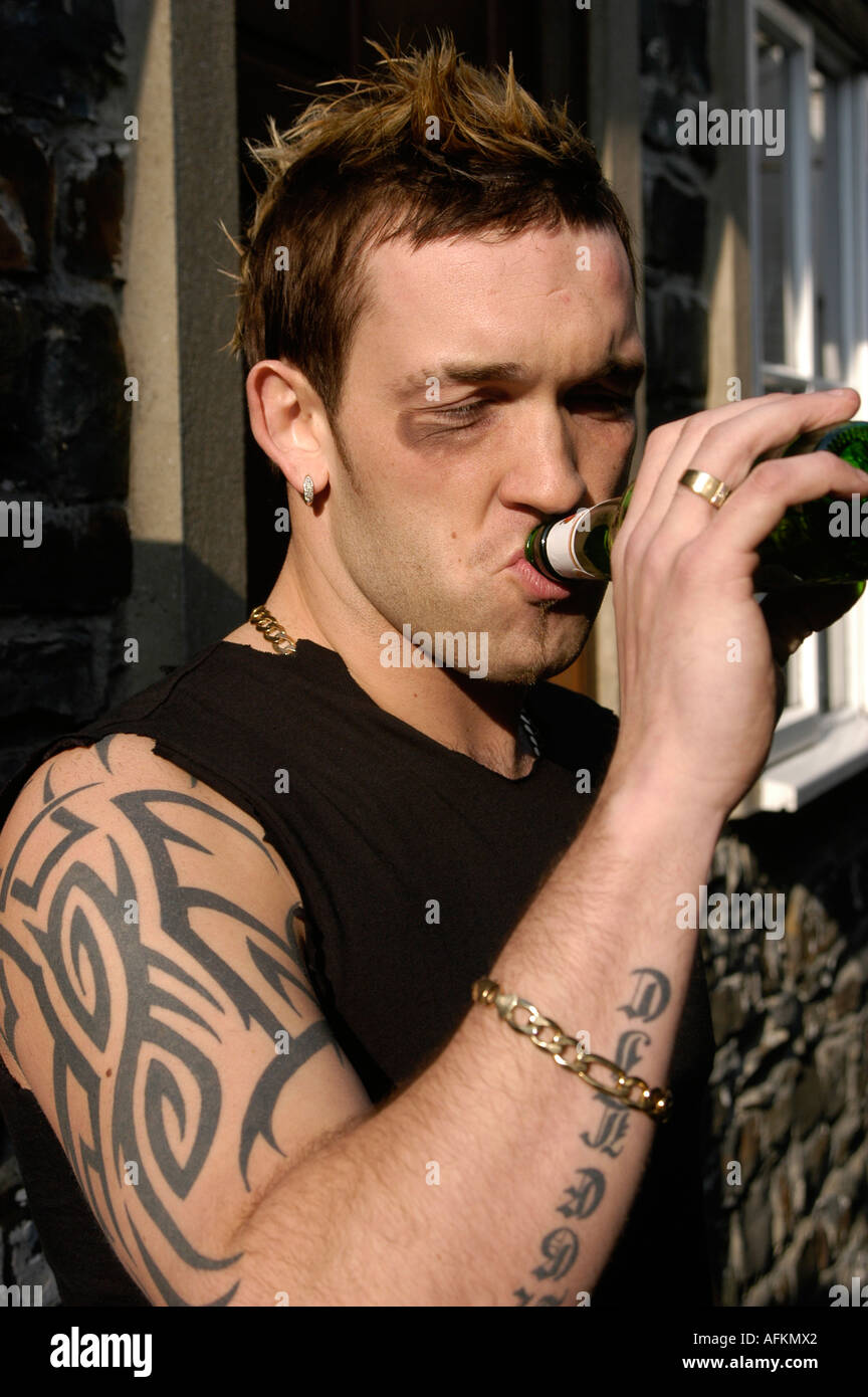 Tribal-Tattoos a-young-male-model-with-tribal-tattoos-on-his-arm-drinking-a-bottle-AFKMX2