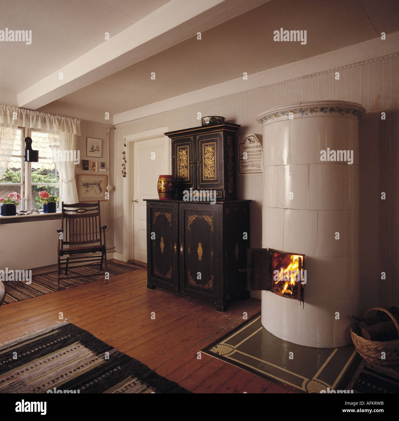 Tall white ceramic stove and antique painted cupboard in rustic ...