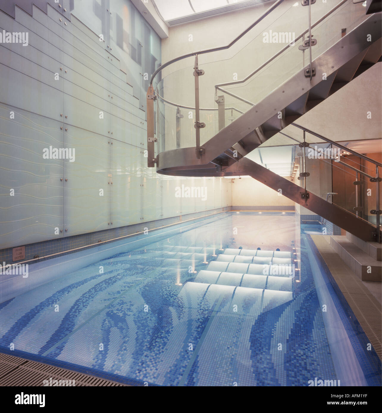 glass and steel cantilevered staircase in modern hotel indoor swimming pool