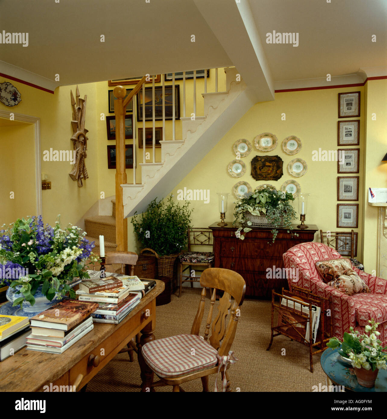Flower Arrangement And Books On Pine Table In Pastel Yellow Cottage Living  Room Pink Armchair And