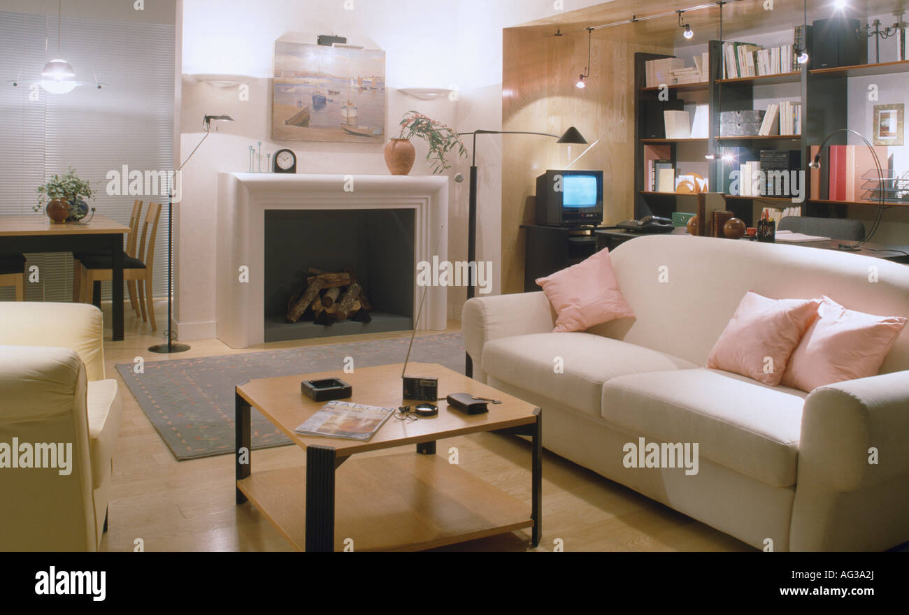 Pink cushions on white sofa beside fireplace in modern Pink room with white furniture