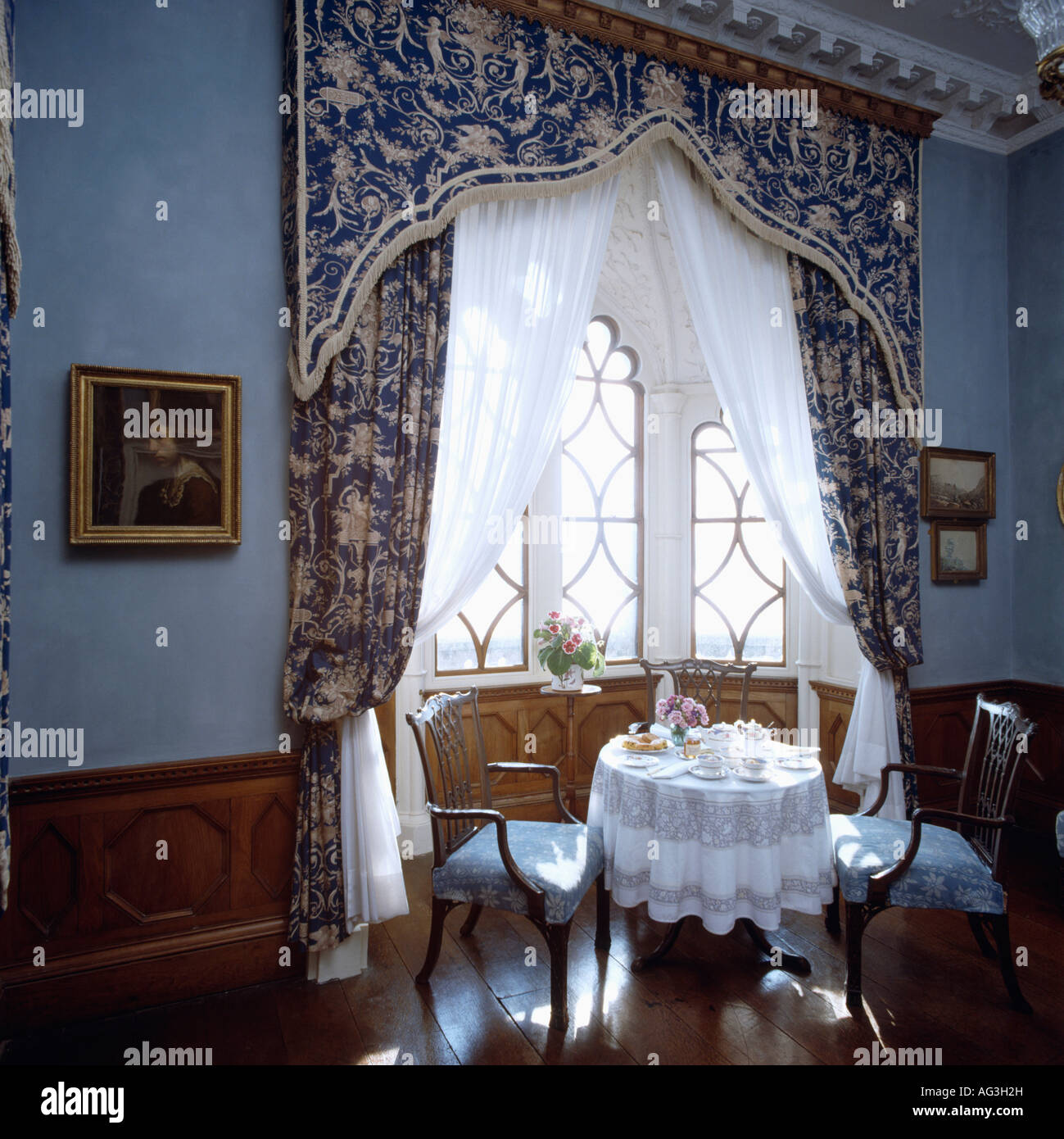 Gothic pelmet above patterned blue drapes in blue diningroom at St ...