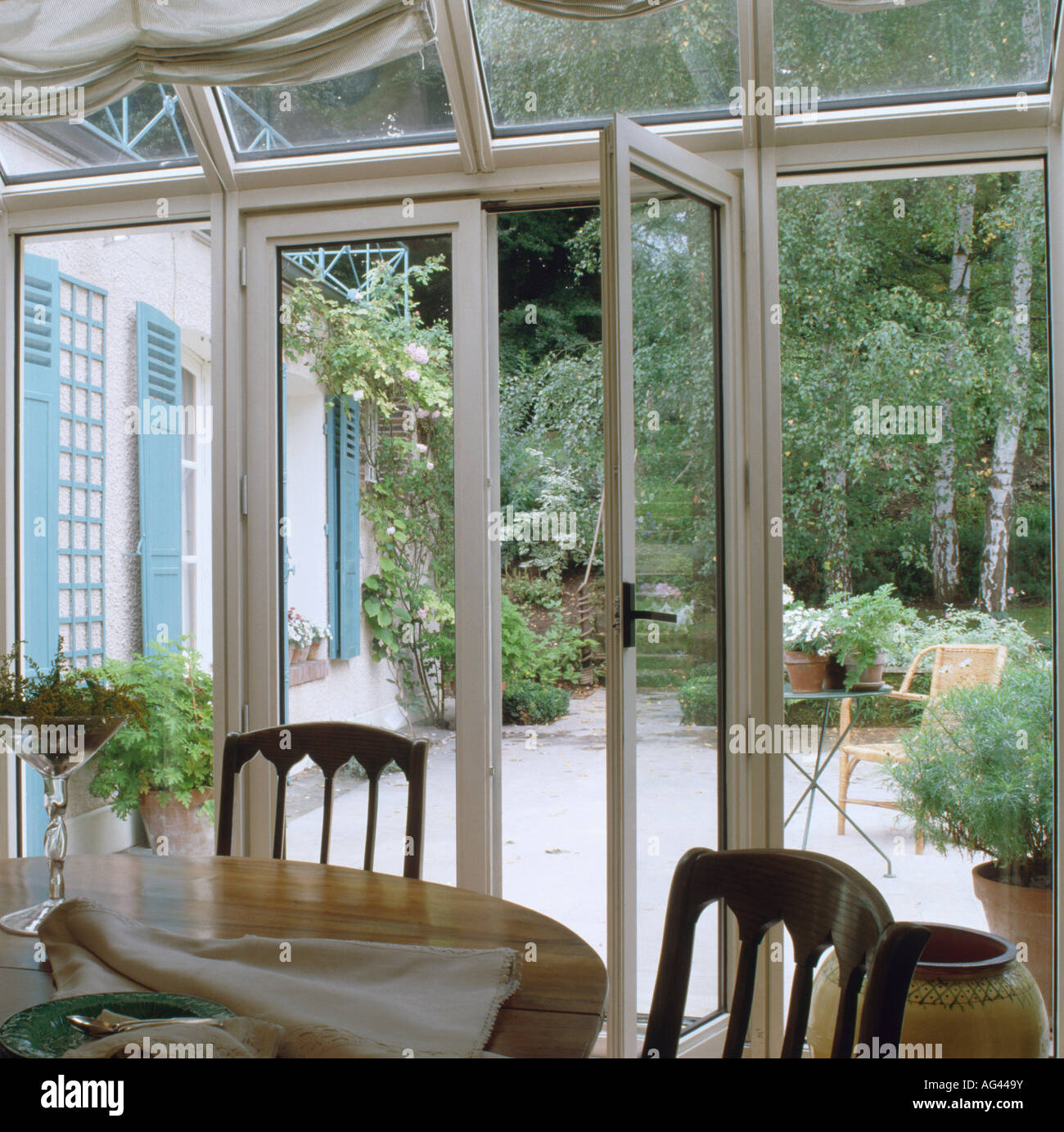 Glass French Doors In Conservatory Dining Room With View Of Patio Garden