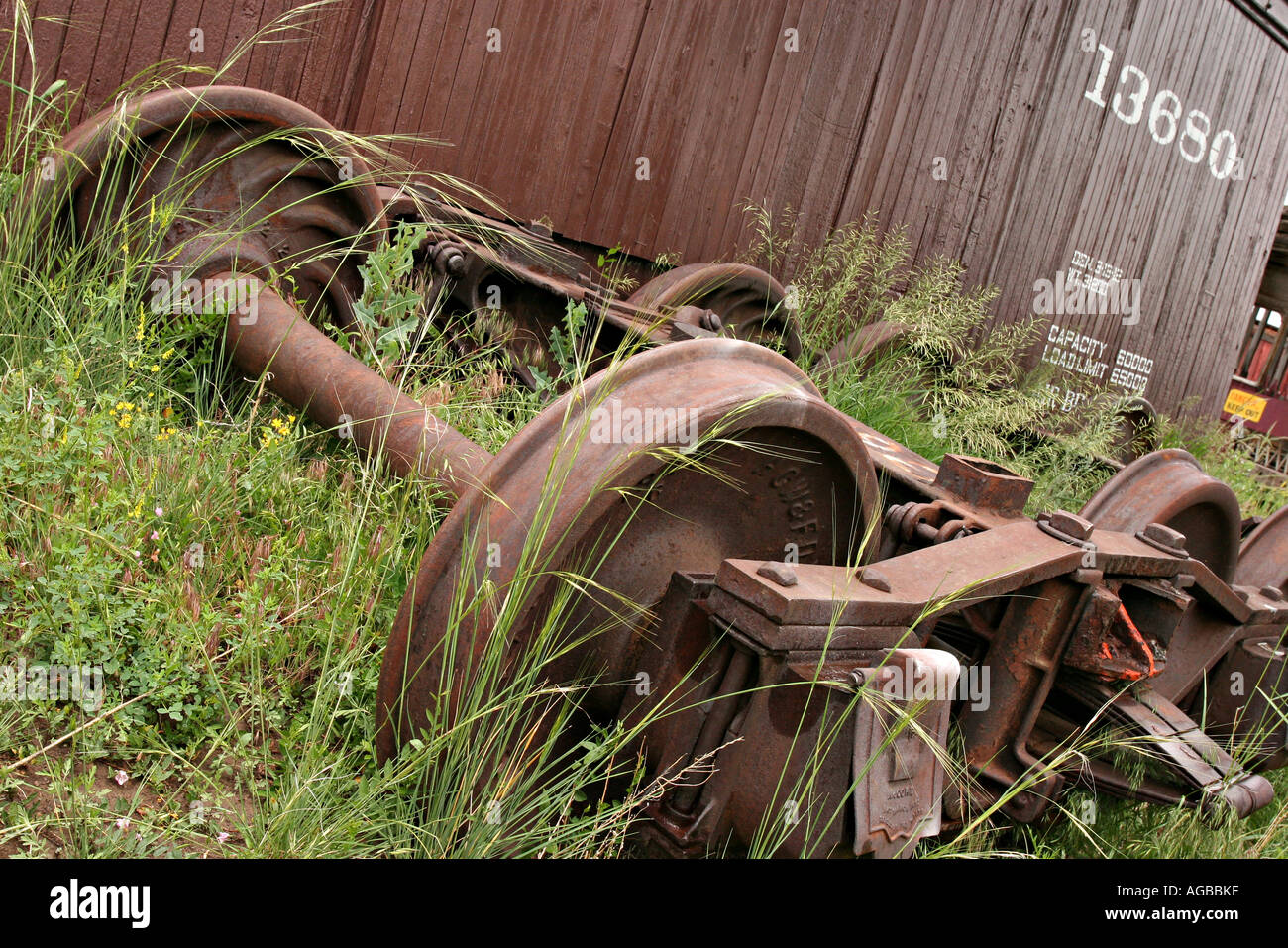 Set Of Train Wheels In The Weeds Next To An Aging Box Car In A