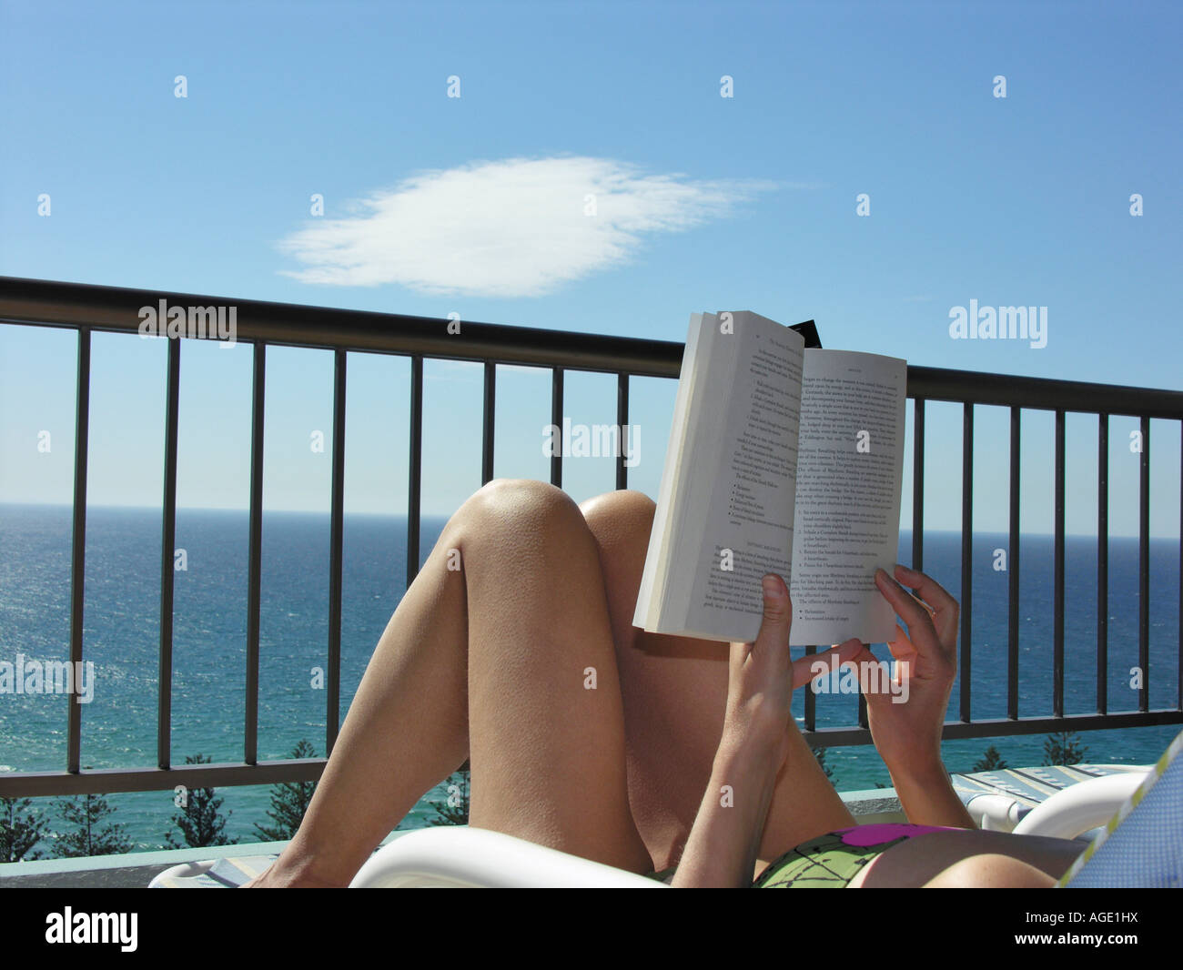 Young woman reading book on balcony over sea lying in deck for The balcony book