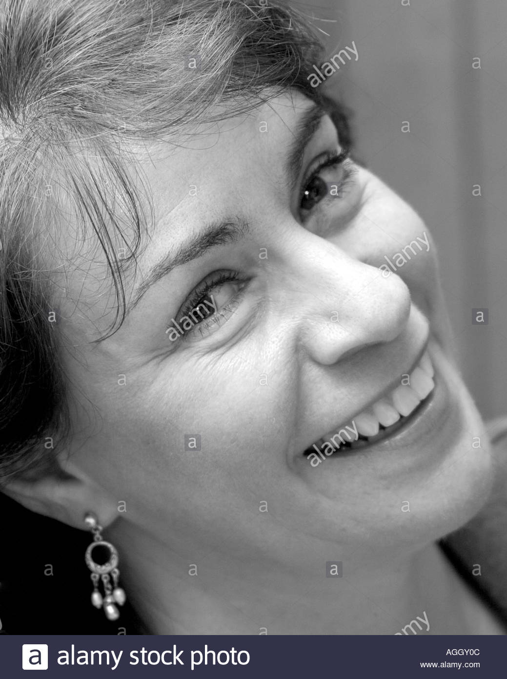 Stock Photo - woman forties or fifties smiling at the camera exuding  confidence and happiness