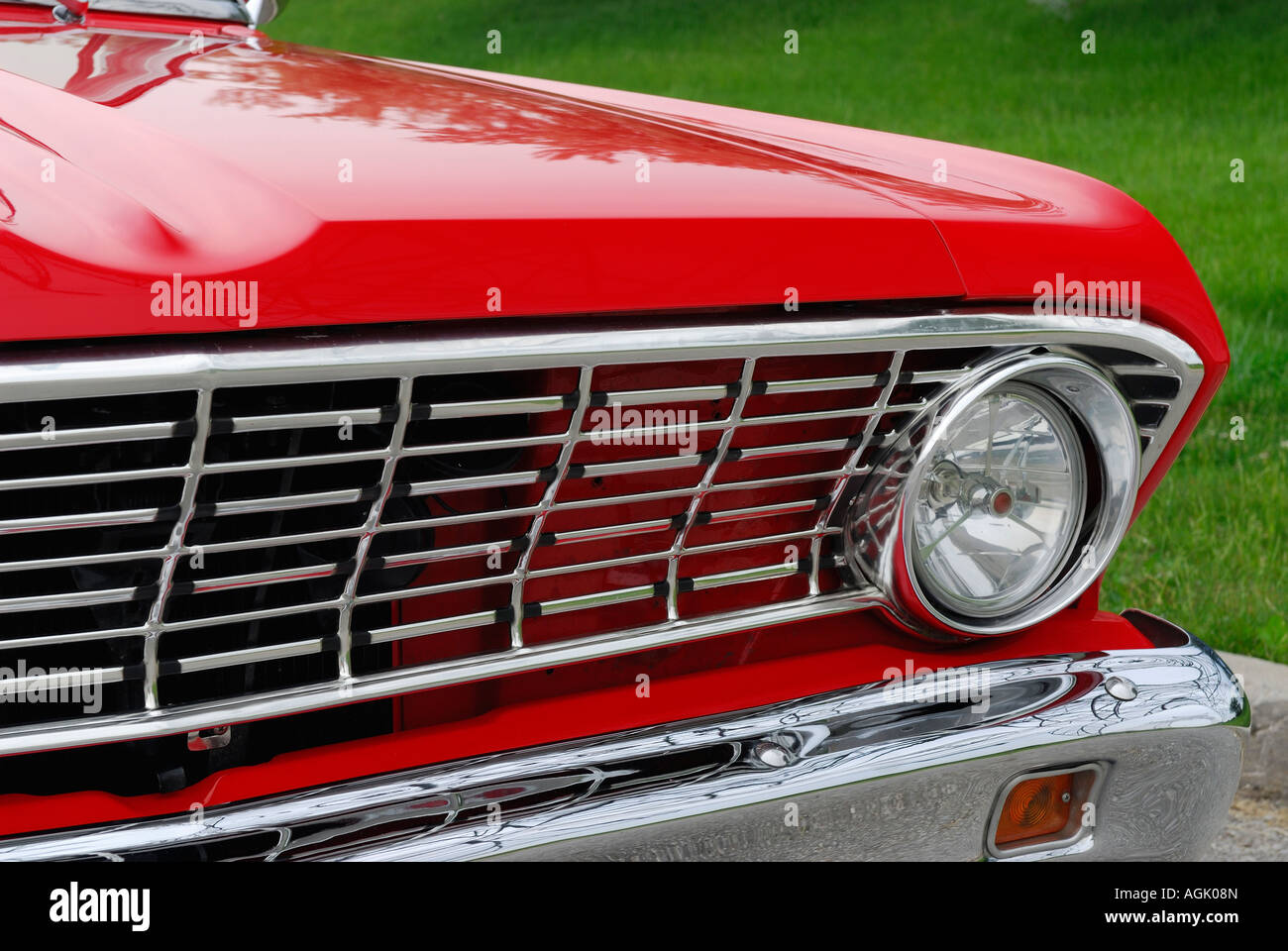 Refurbished red 1964 ford falcon car front grill and hood against refurbished red 1964 ford falcon car front grill and hood against green grass sciox Images