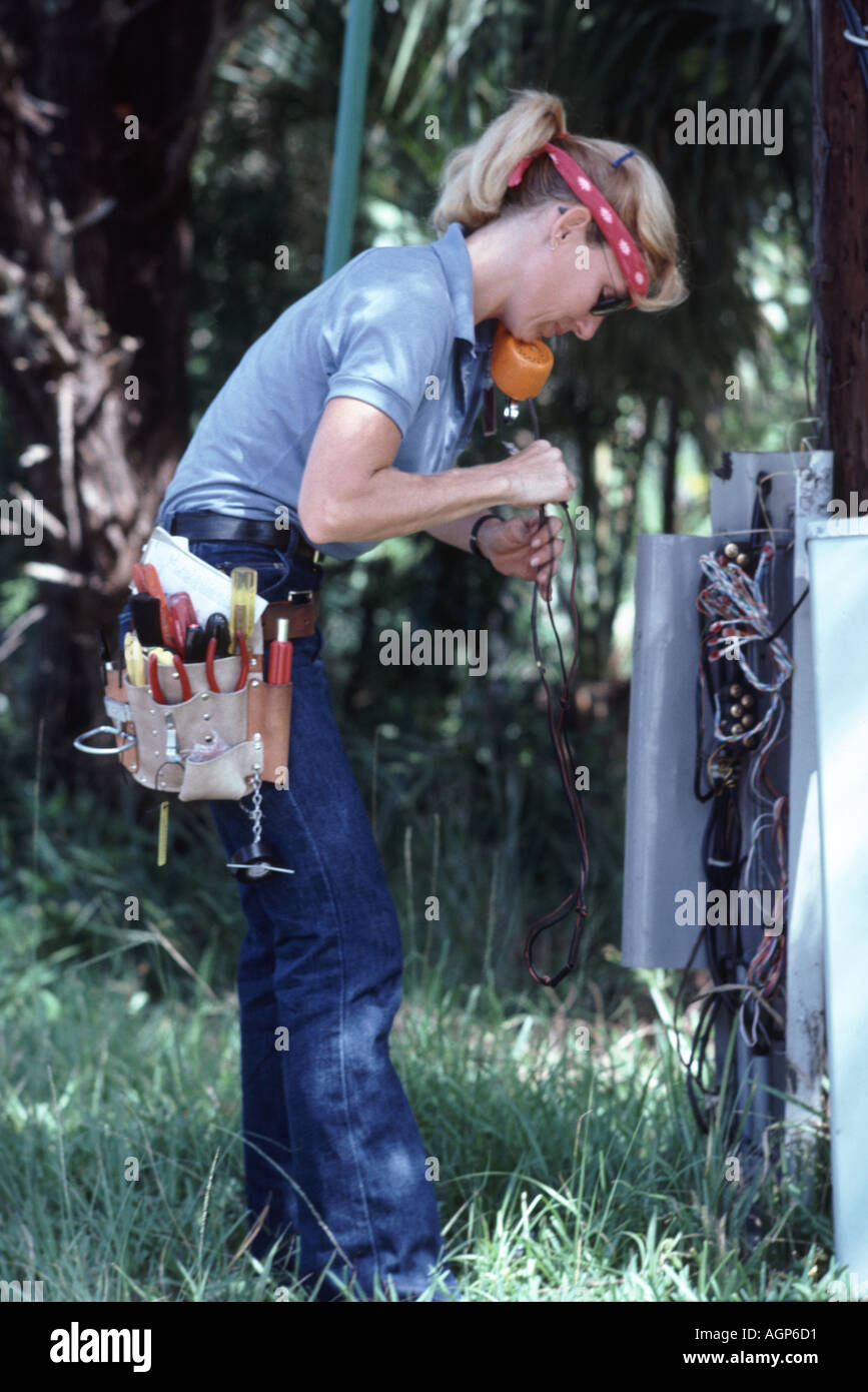 Woman telephone technician checking phone lines at switchbox on ...