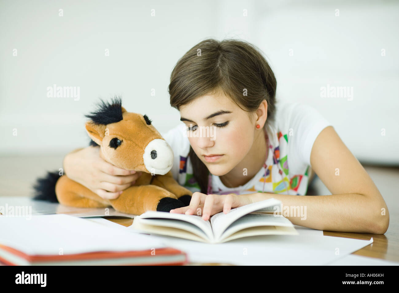 Young woman lying on floor listening to headphones and doing homework  Royalty free stock photo