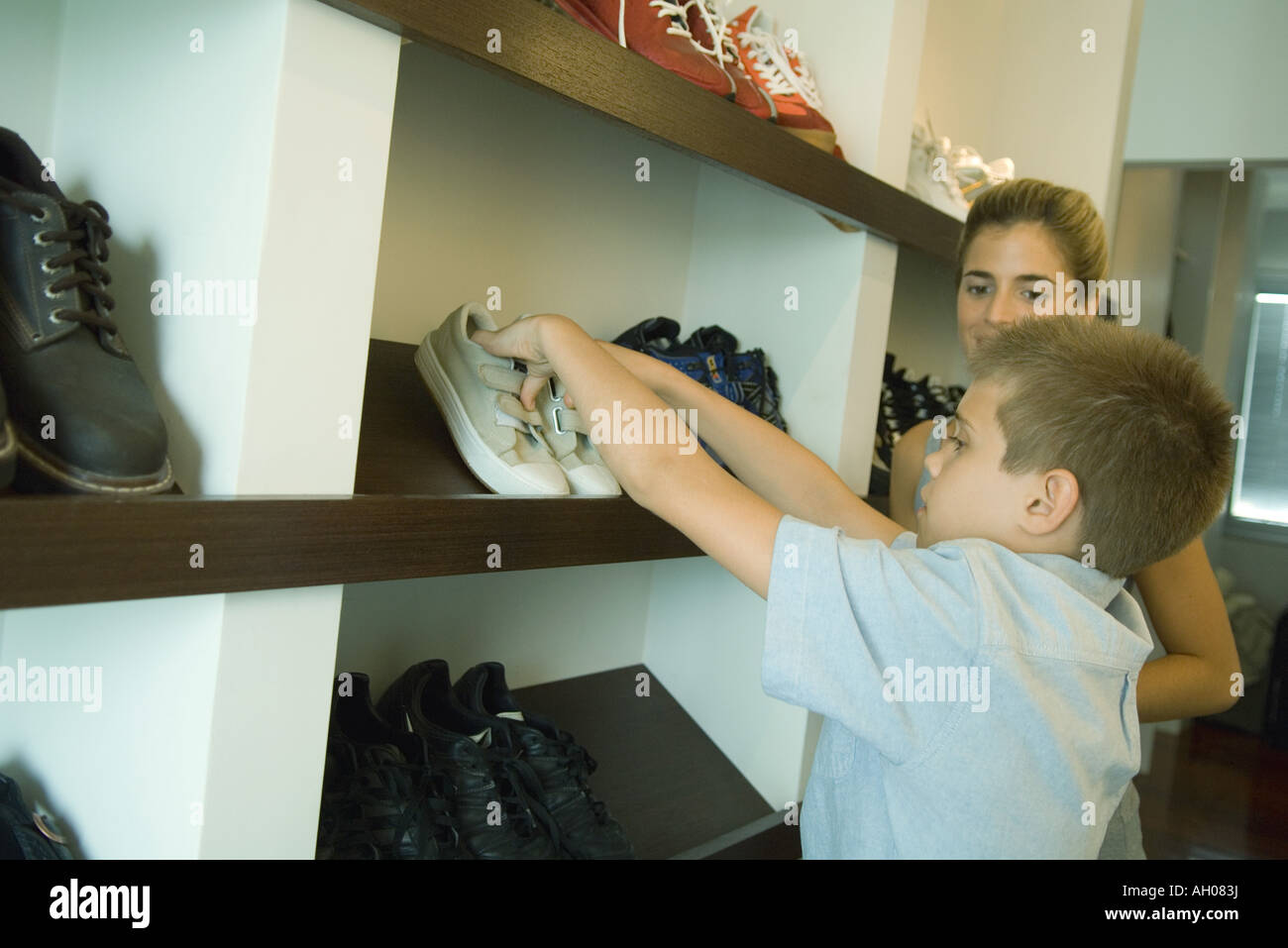 Boy putting shoes on shoe rack while mother watches Stock ... | 1300 x 957 jpeg 105kB